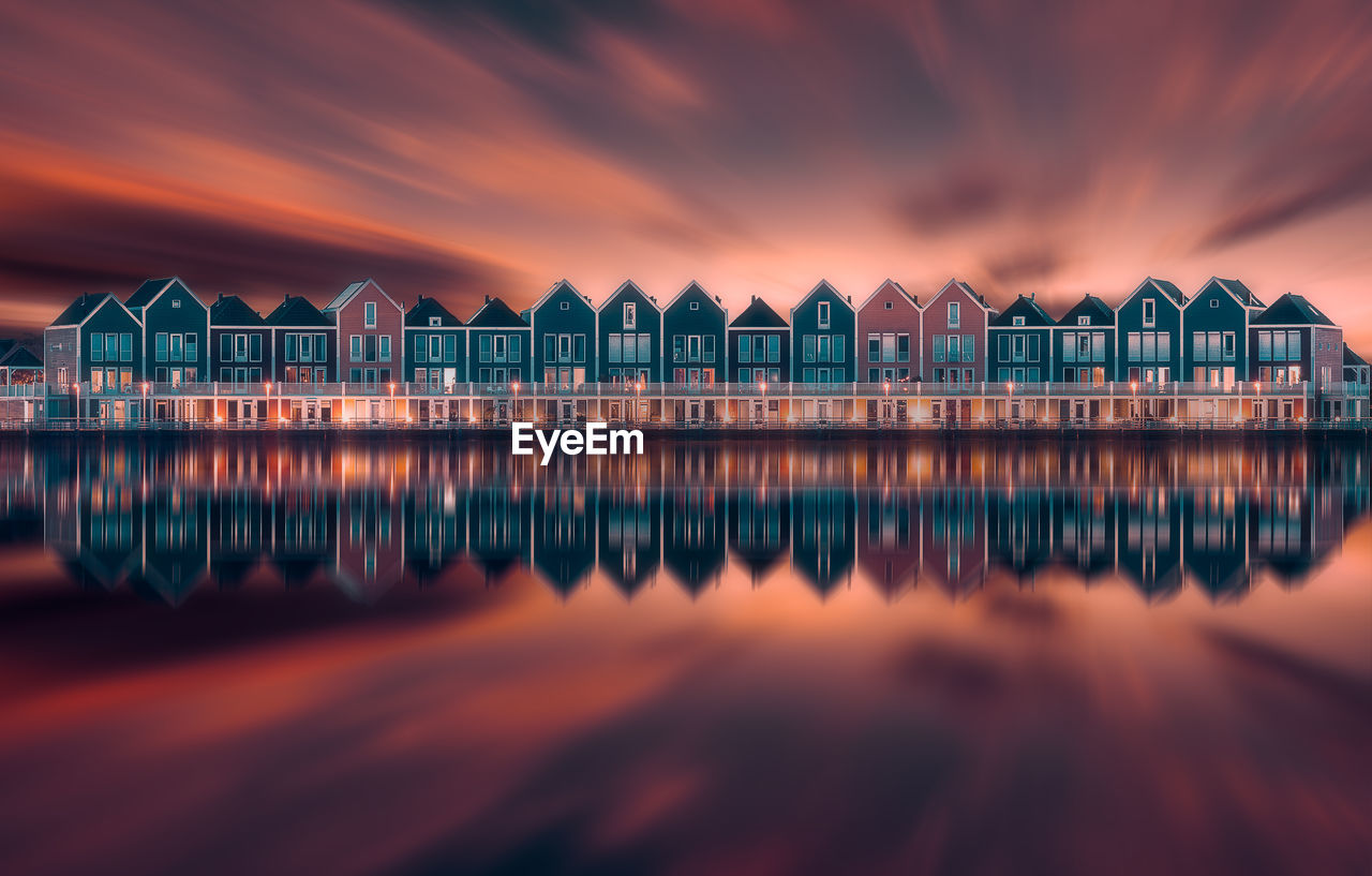 Scenic View Of Houses Reflecting On Sea Against Orange Sky