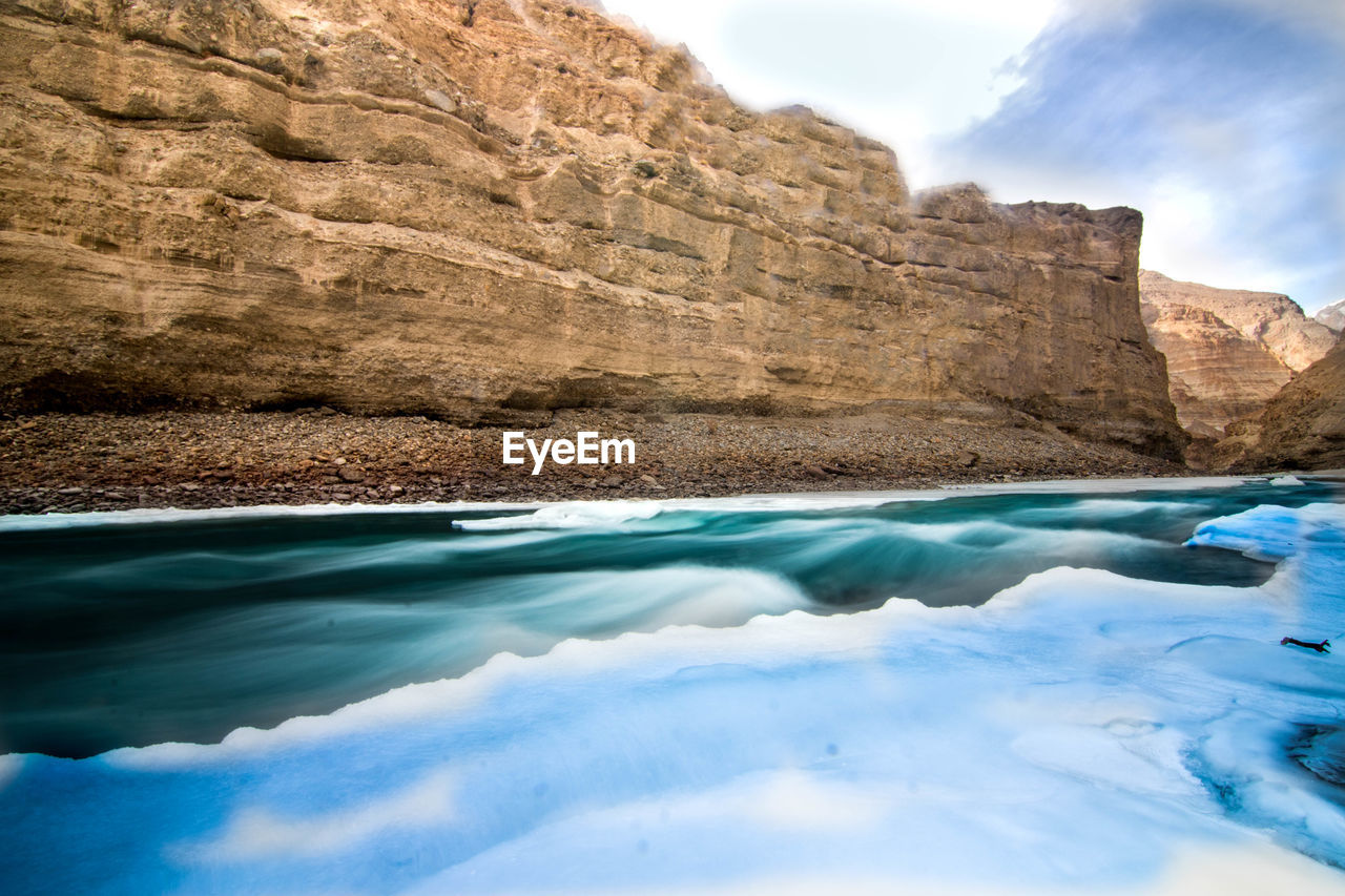 water, beauty in nature, rock, scenics - nature, tranquility, solid, nature, rock - object, tranquil scene, rock formation, sea, waterfront, mountain, non-urban scene, sky, no people, day, idyllic, cloud - sky, outdoors, formation, turquoise colored, eroded, swimming pool