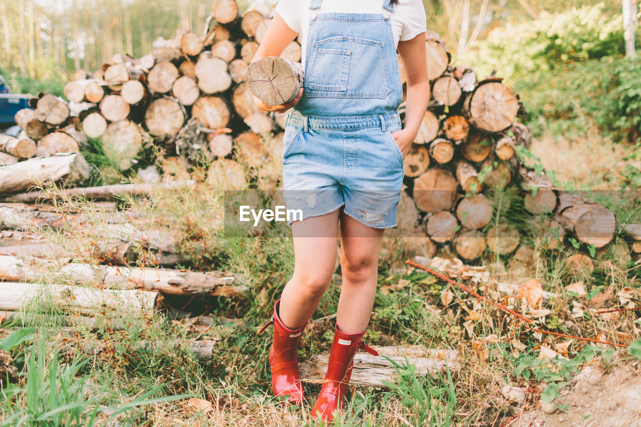 Low Section Of Girl Carrying Log While Standing On Field