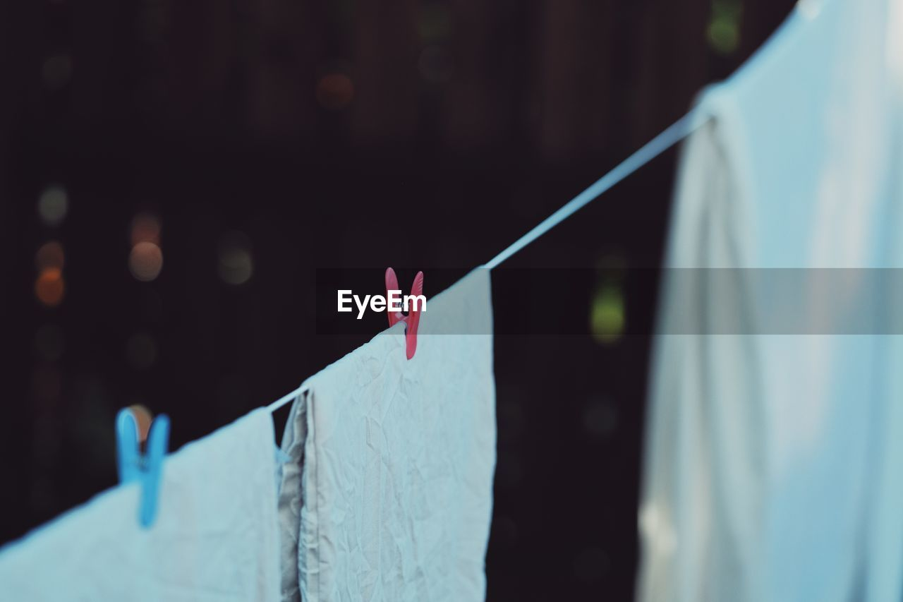 clothesline, clothespin, hanging, clothing, drying, laundry, textile, focus on foreground, no people, close-up, white color, selective focus, day, coathanger, nature, outdoors, blue, rope, in a row, paper, clean, consumerism