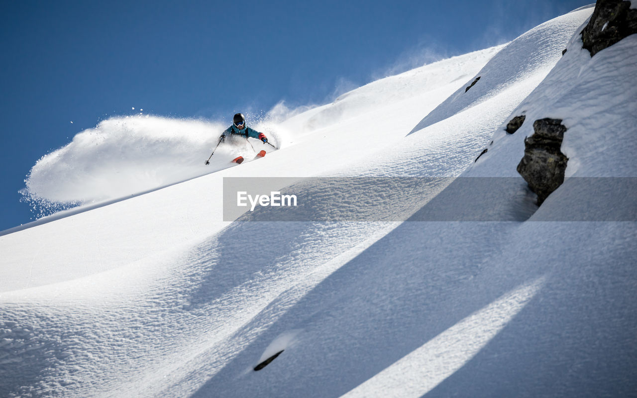 Low angle view of man skiing on snow covered mountain