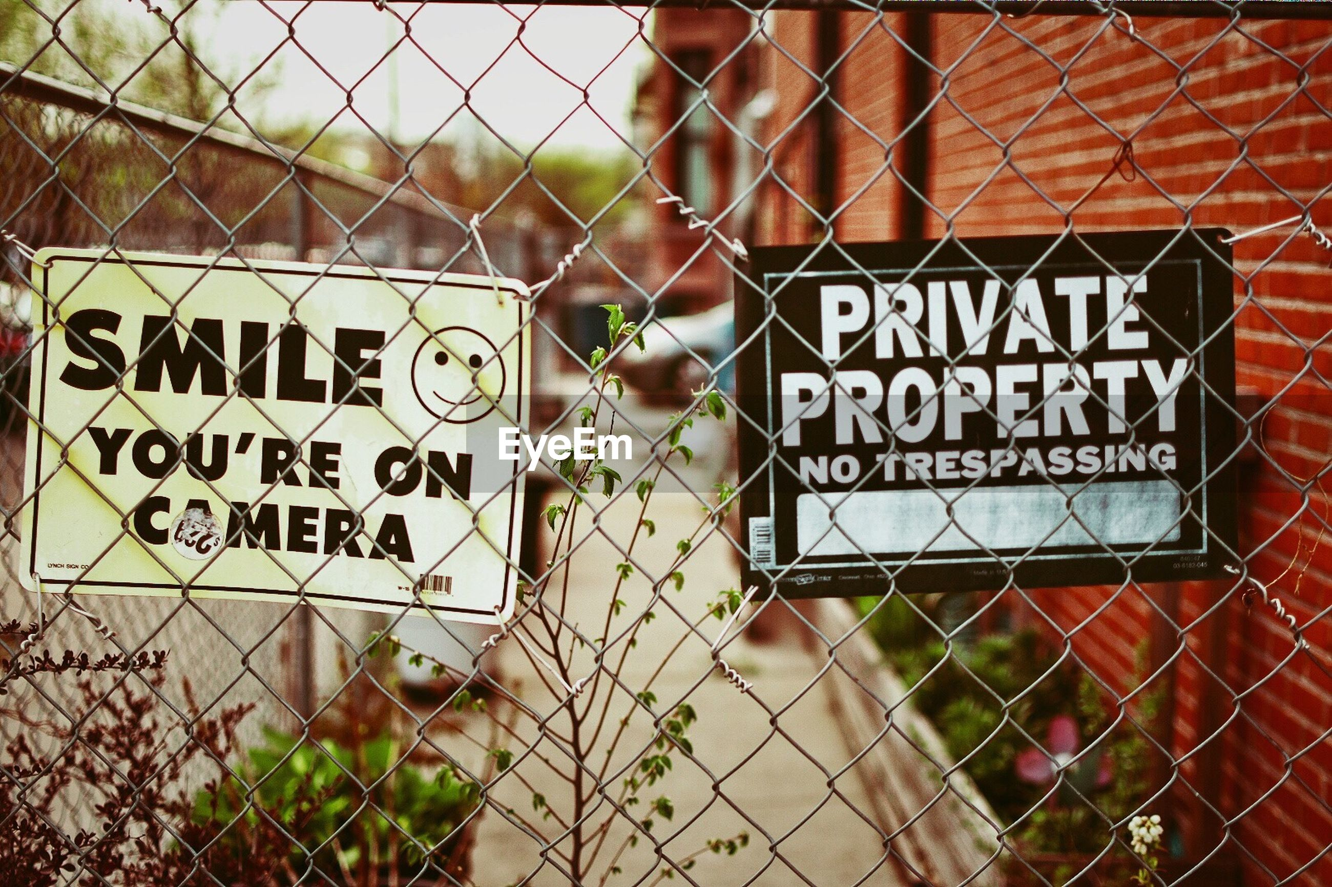 CLOSE-UP OF WARNING SIGN ON CHAINLINK FENCE