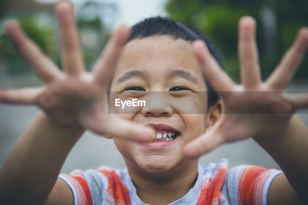 Portrait of smiling boy gesturing while standing outdoors