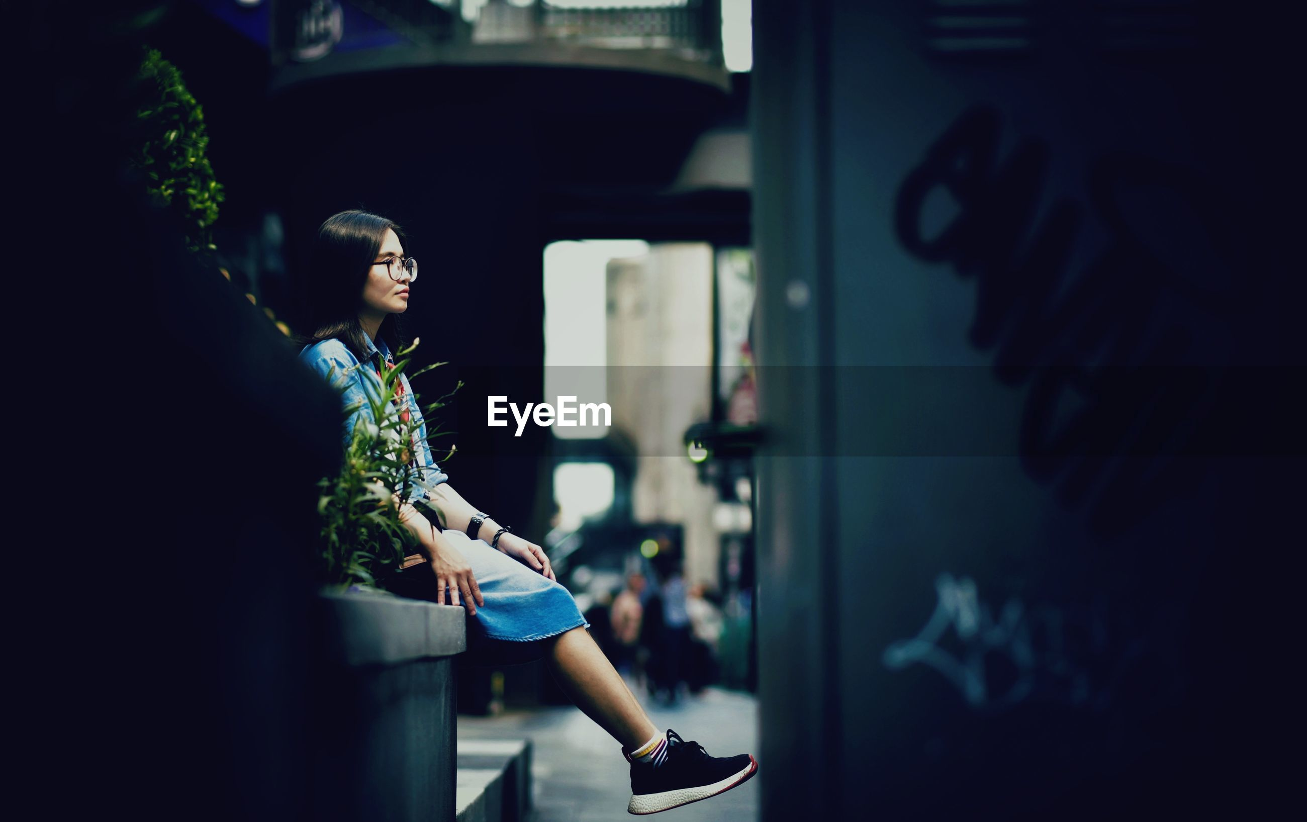 Woman looking away while sitting in city