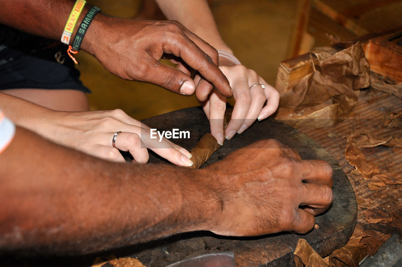 Cropped Image Of People Hands Making Cigar