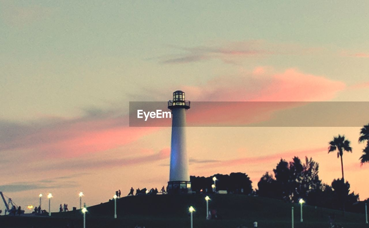 sky, built structure, architecture, building exterior, tower, sunset, cloud - sky, tall - high, guidance, nature, no people, building, low angle view, lighthouse, outdoors, orange color, factory, dusk, smoke stack, city, pollution, architectural column, air pollution