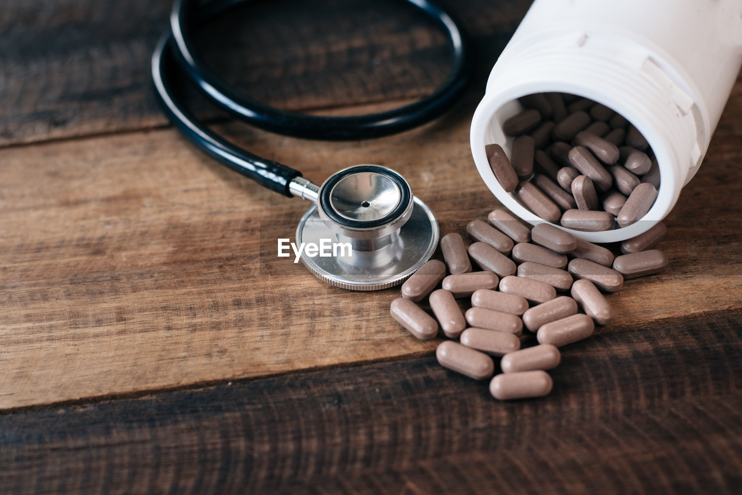 High angle view of capsules with stethoscope on wooden table