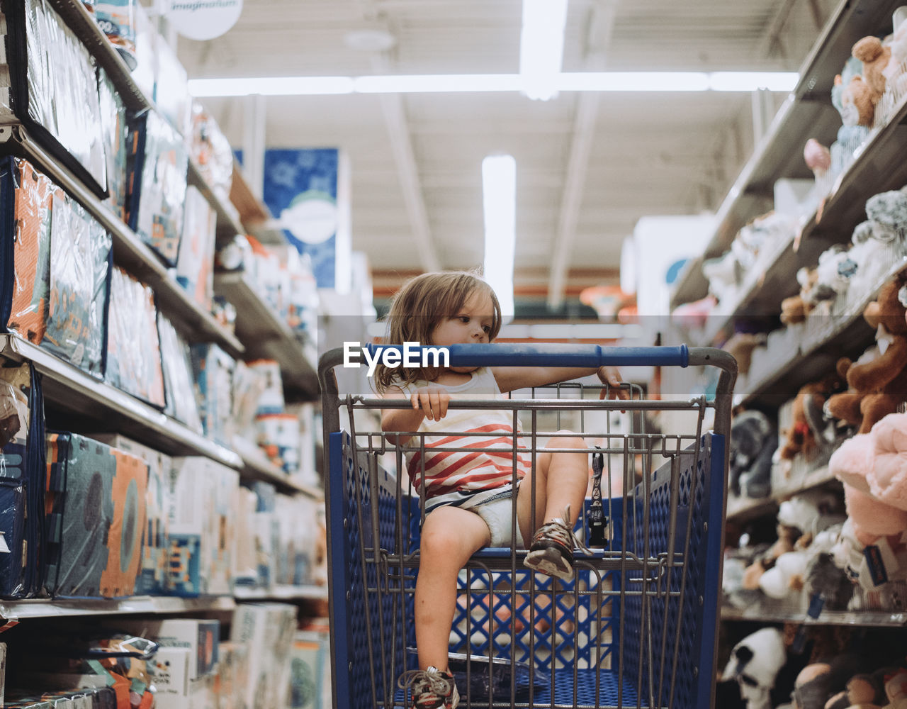 one person, real people, childhood, lifestyles, indoors, store, child, casual clothing, shelf, retail, leisure activity, standing, shopping, women, choice, hairstyle, looking, consumerism, bangs