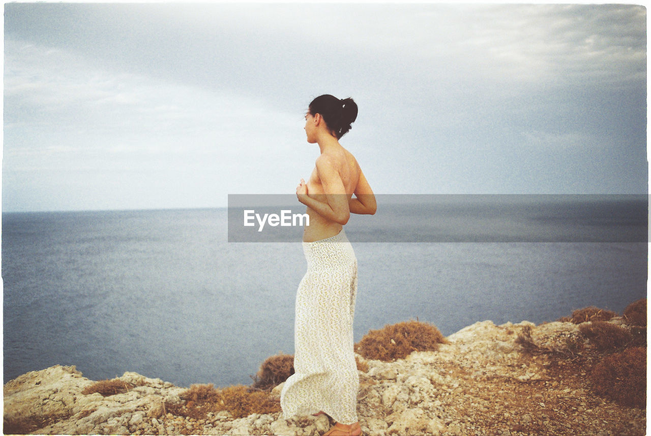 Side View Of Shirtless Woman Standing On Rock Formation Against Sky