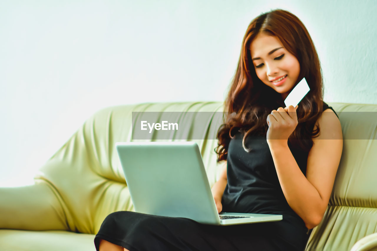 wireless technology, communication, technology, connection, young adult, laptop, one person, young women, front view, sitting, indoors, portable information device, furniture, computer, using laptop, holding, mobile phone, real people, using phone, three quarter length, beautiful woman, surfing the net, hairstyle