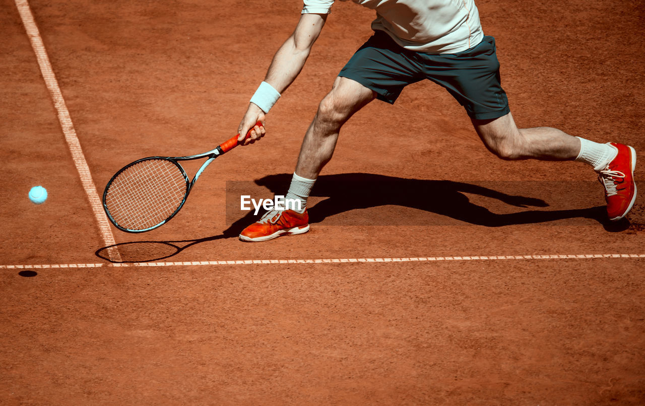 Low section of man playing tennis in court