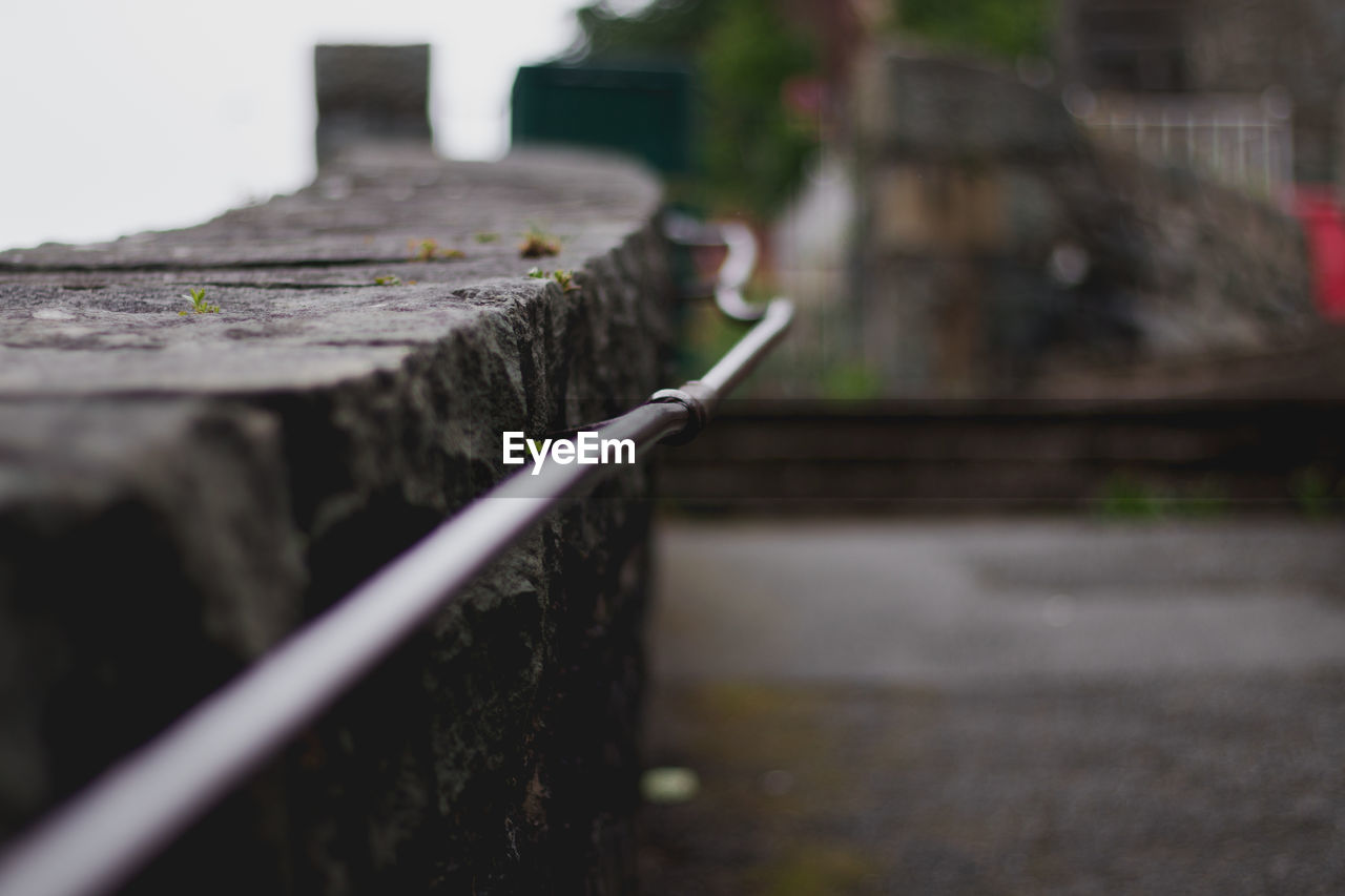 selective focus, architecture, no people, built structure, day, wood - material, focus on foreground, close-up, outdoors, nature, metal, barrier, boundary, fence, railing, plant, building exterior, wall - building feature, city, connection