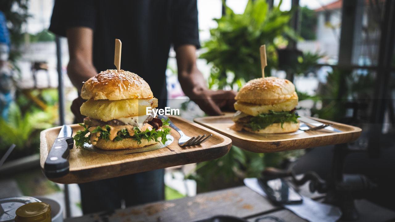 Midsection Of Waiter Serving Burger At Restaurant