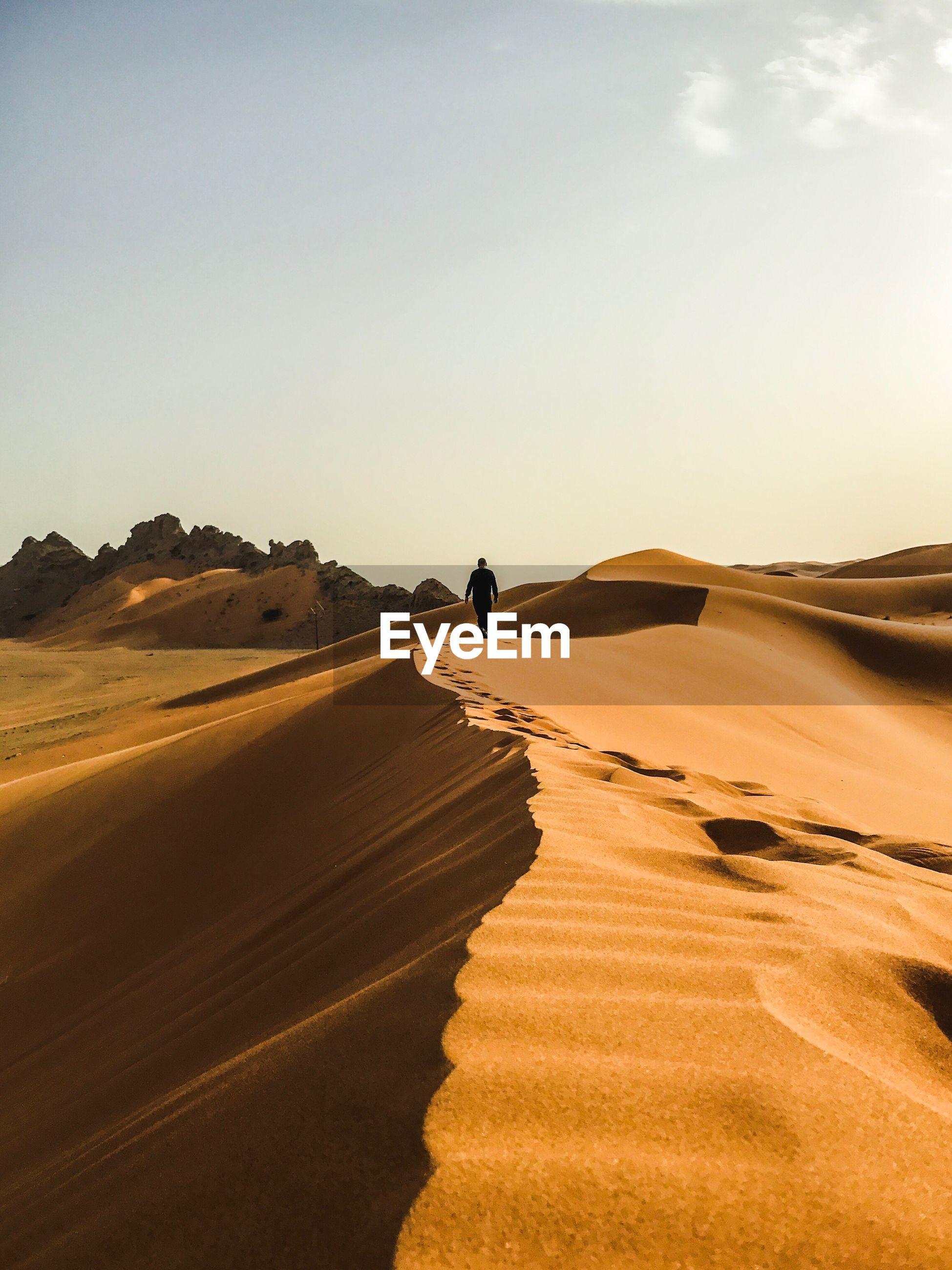 Man walking on desert against clear sky