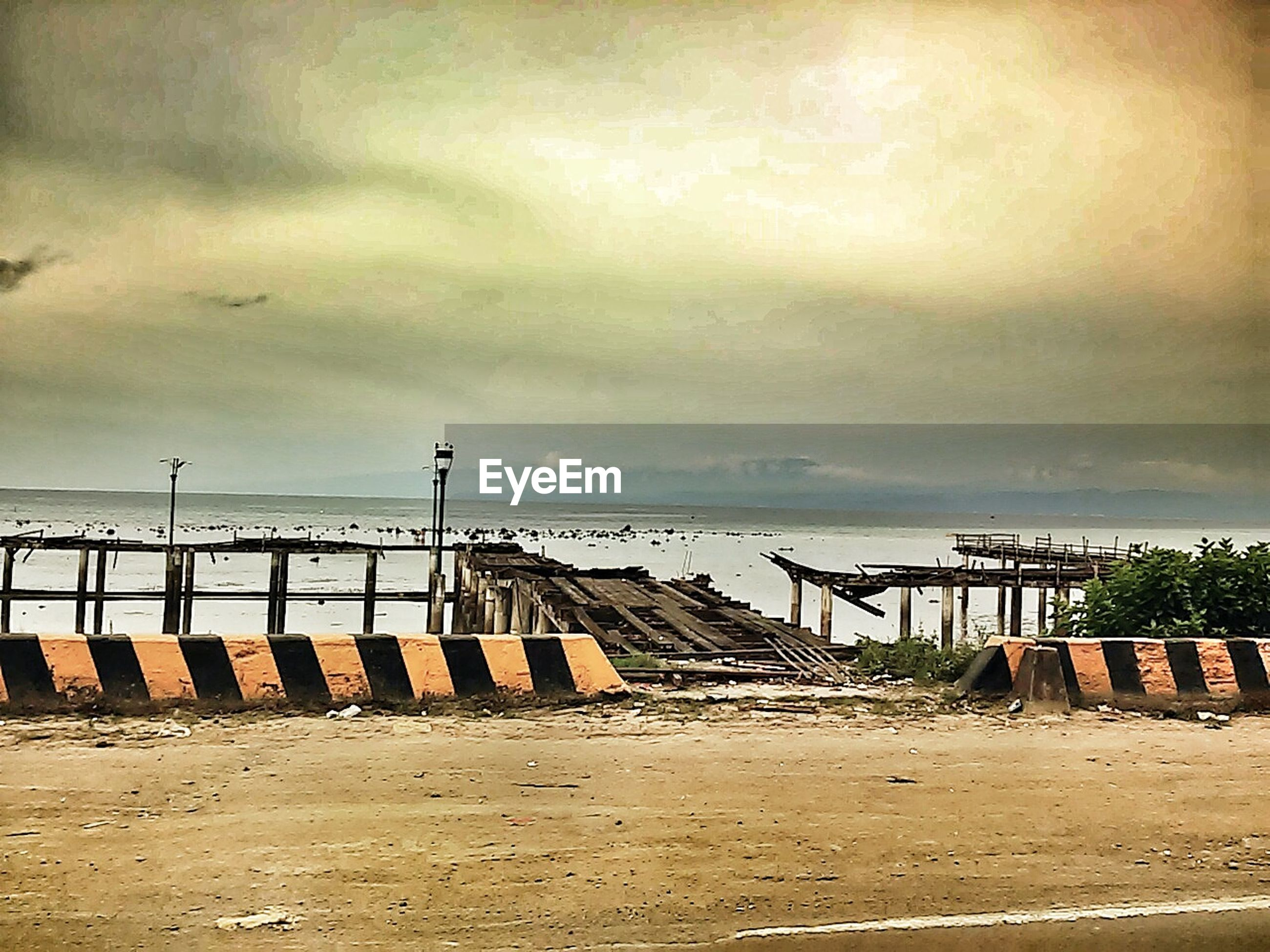 Damaged pier on sea against cloudy sky during sunset