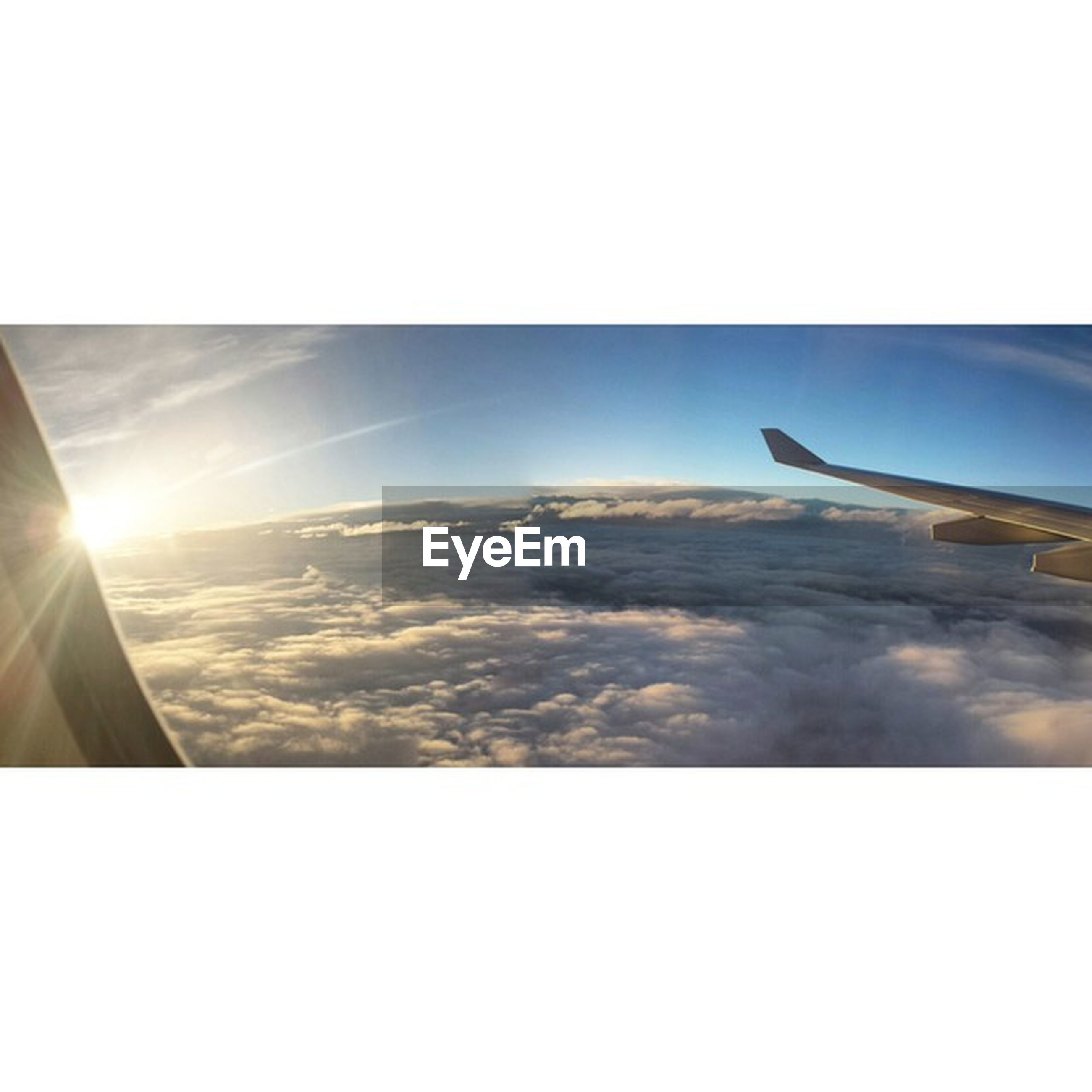 airplane, aircraft wing, flying, transportation, air vehicle, mode of transport, sun, part of, sunlight, sky, scenics, beauty in nature, cropped, sea, mid-air, nature, travel, clear sky, aerial view, journey