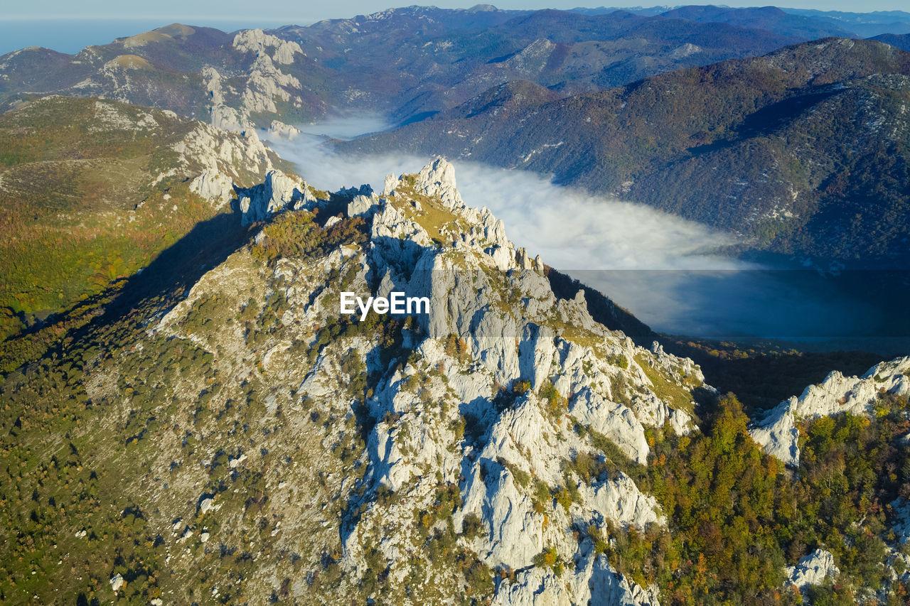 Dabarski kukovi rocks with the mist in the valley on the velebit mountain, croatia