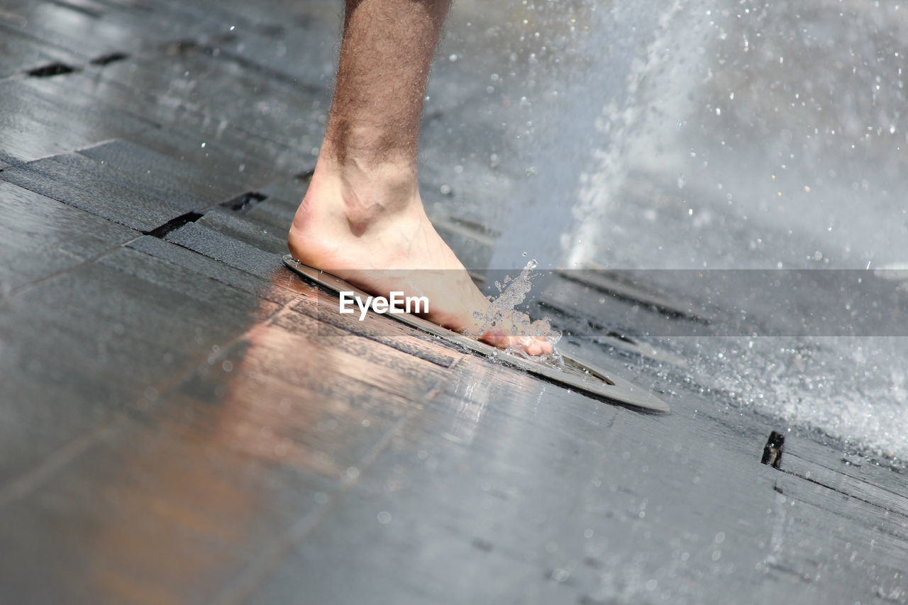 Low Section Of Man Stepping On Fountain