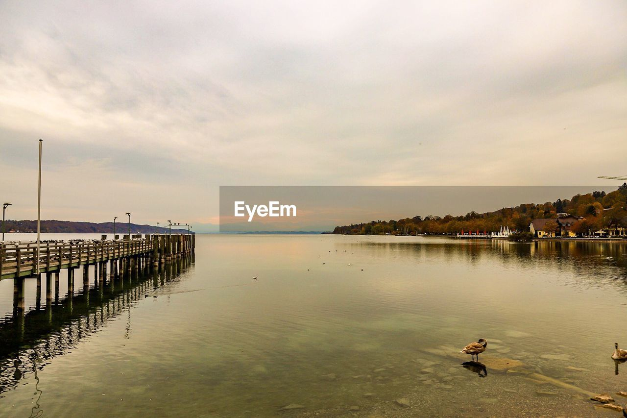 water, sky, cloud - sky, beauty in nature, scenics - nature, nature, architecture, sea, built structure, tranquility, sunset, waterfront, tranquil scene, reflection, pier, outdoors, beach, real people, day