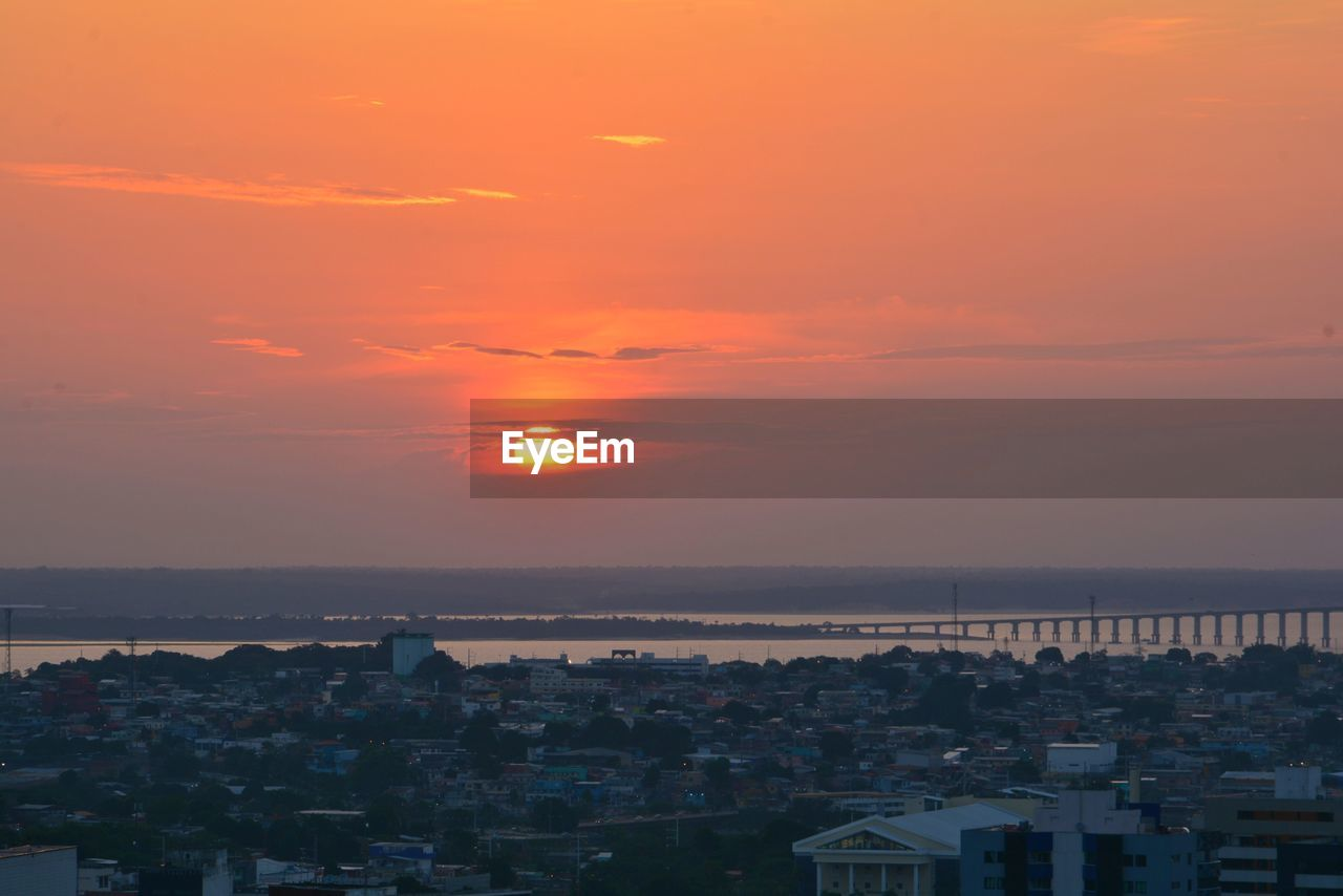 sky, sunset, building exterior, architecture, built structure, orange color, city, sea, beauty in nature, water, scenics - nature, residential district, building, no people, cloud - sky, nature, horizon over water, high angle view, sun, outdoors, cityscape, romantic sky, townscape