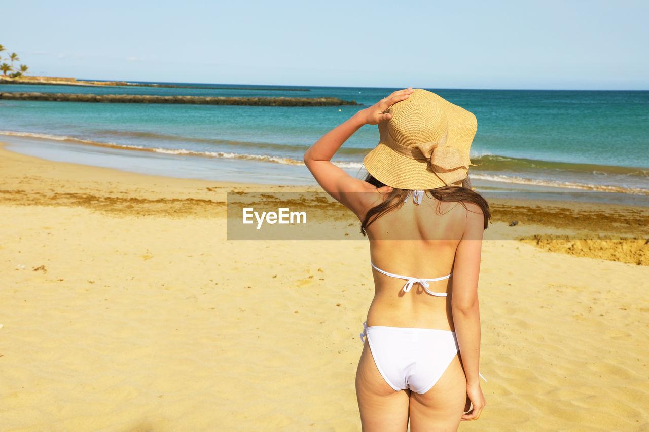 Rear View Of Woman In Bikini Standing On Beach