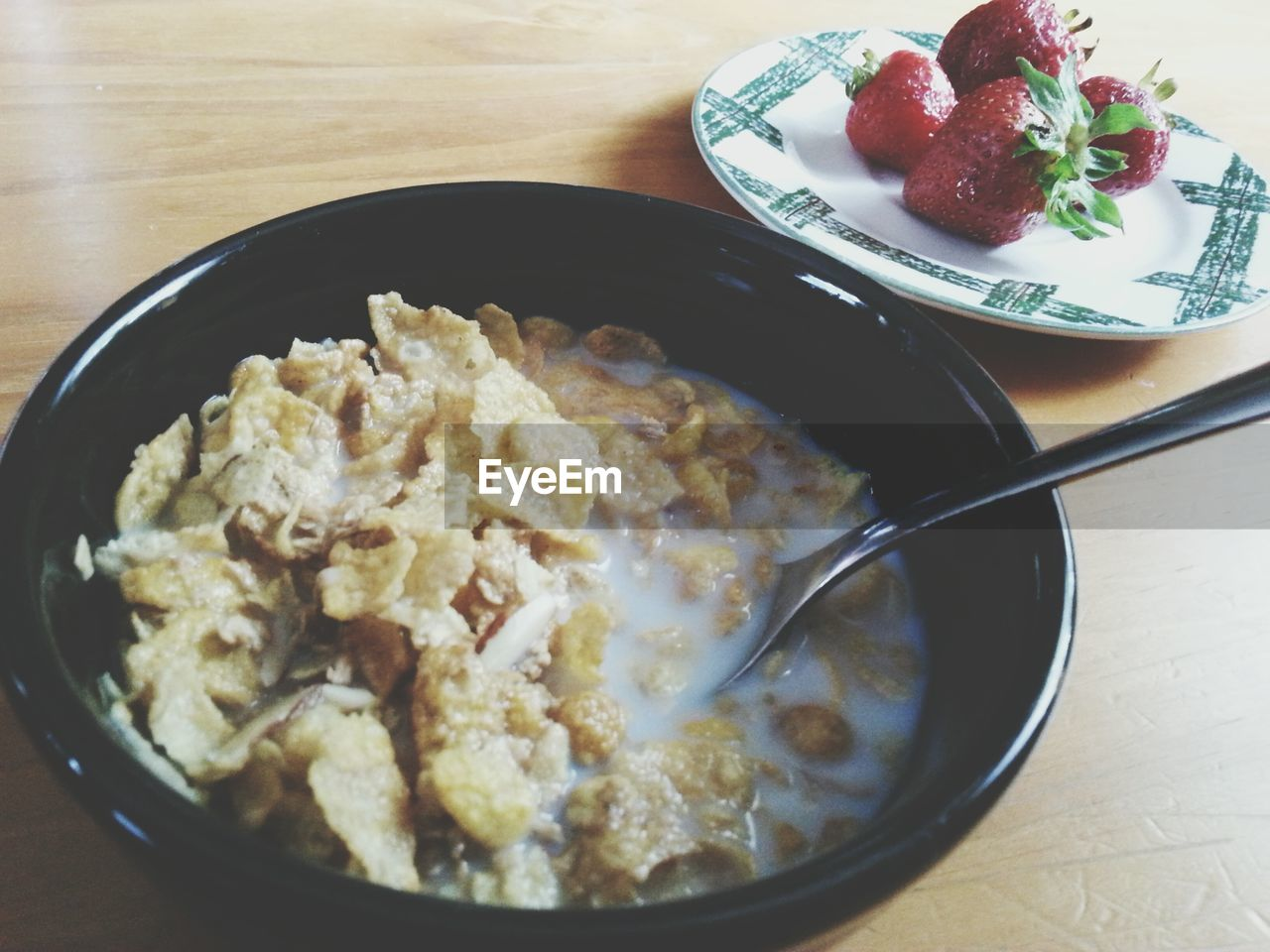 Close-Up Of Corn Flakes In Bowl With Strawberries At Table