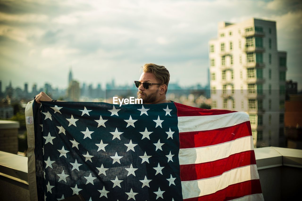 one person, focus on foreground, architecture, real people, men, striped, front view, glasses, young adult, built structure, lifestyles, casual clothing, patriotism, sky, city, building exterior, day, flag, outdoors