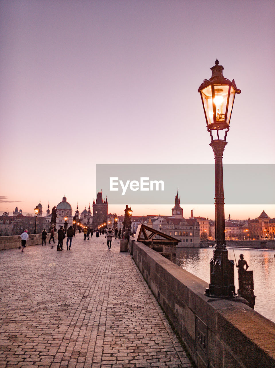 People on street light in city at sunset