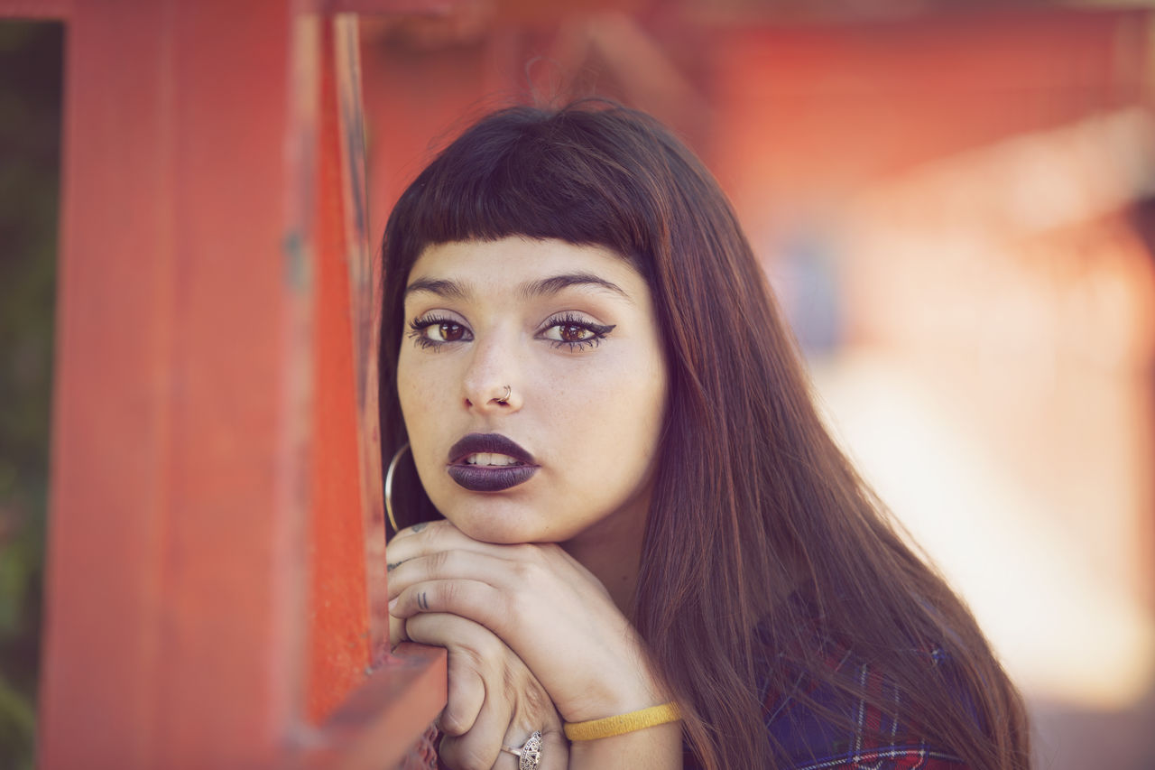 Close-up portrait of young woman leaning on railing at footbridge