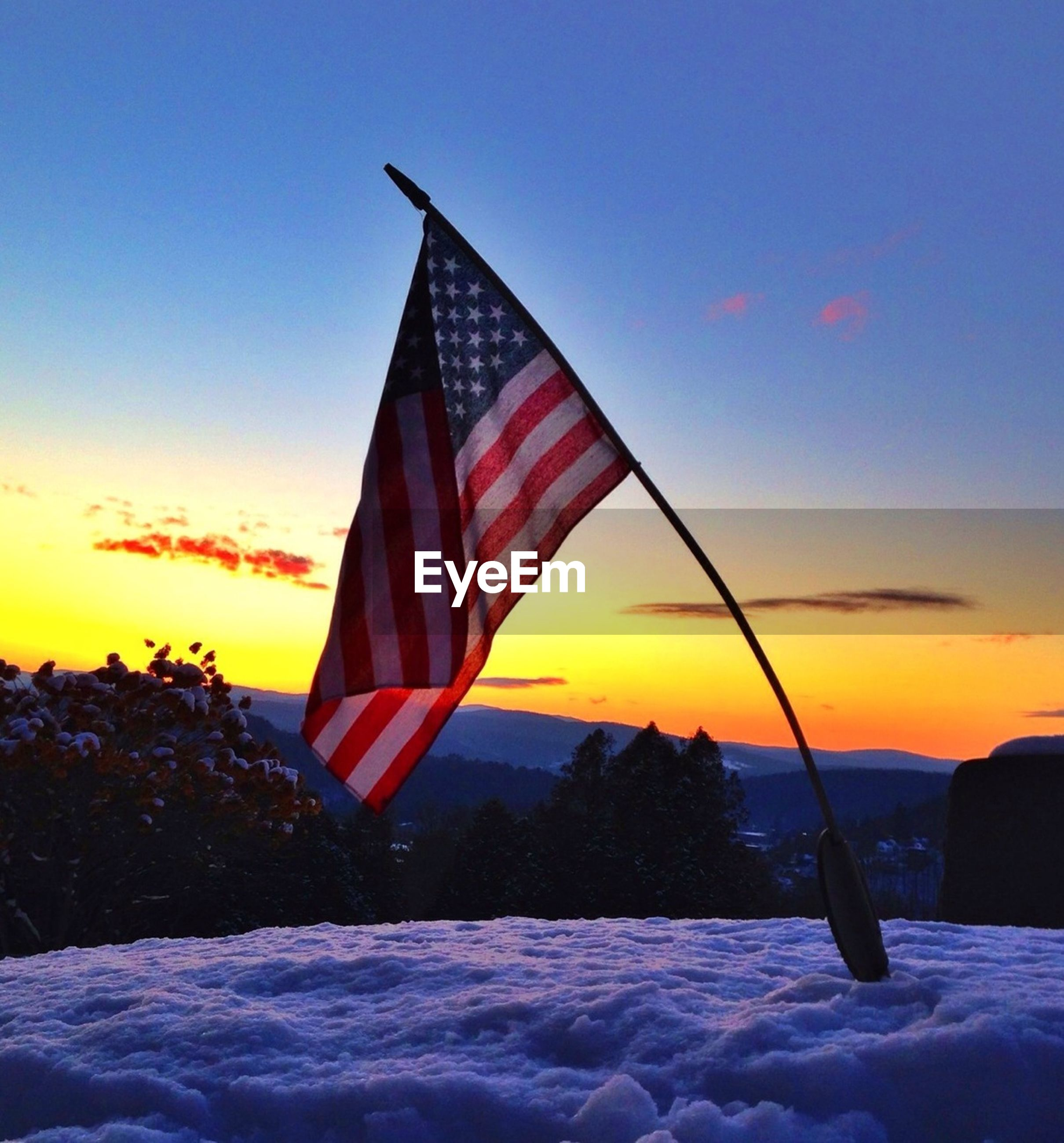 flag, patriotism, sky, identity, national flag, low angle view, cloud, blue, cloud - sky, sunlight, red, nature, american flag, no people, outdoors, tranquility, sunset, beauty in nature, wind, tree