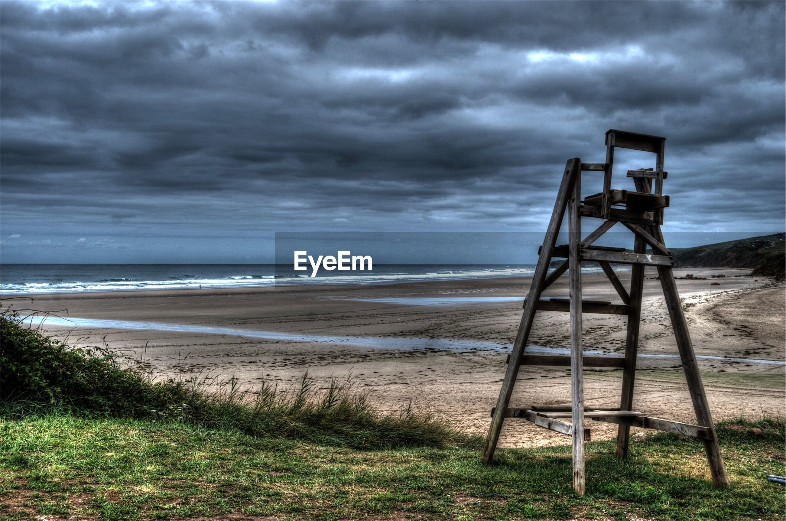 Rescue tower at beach against cloudy sky