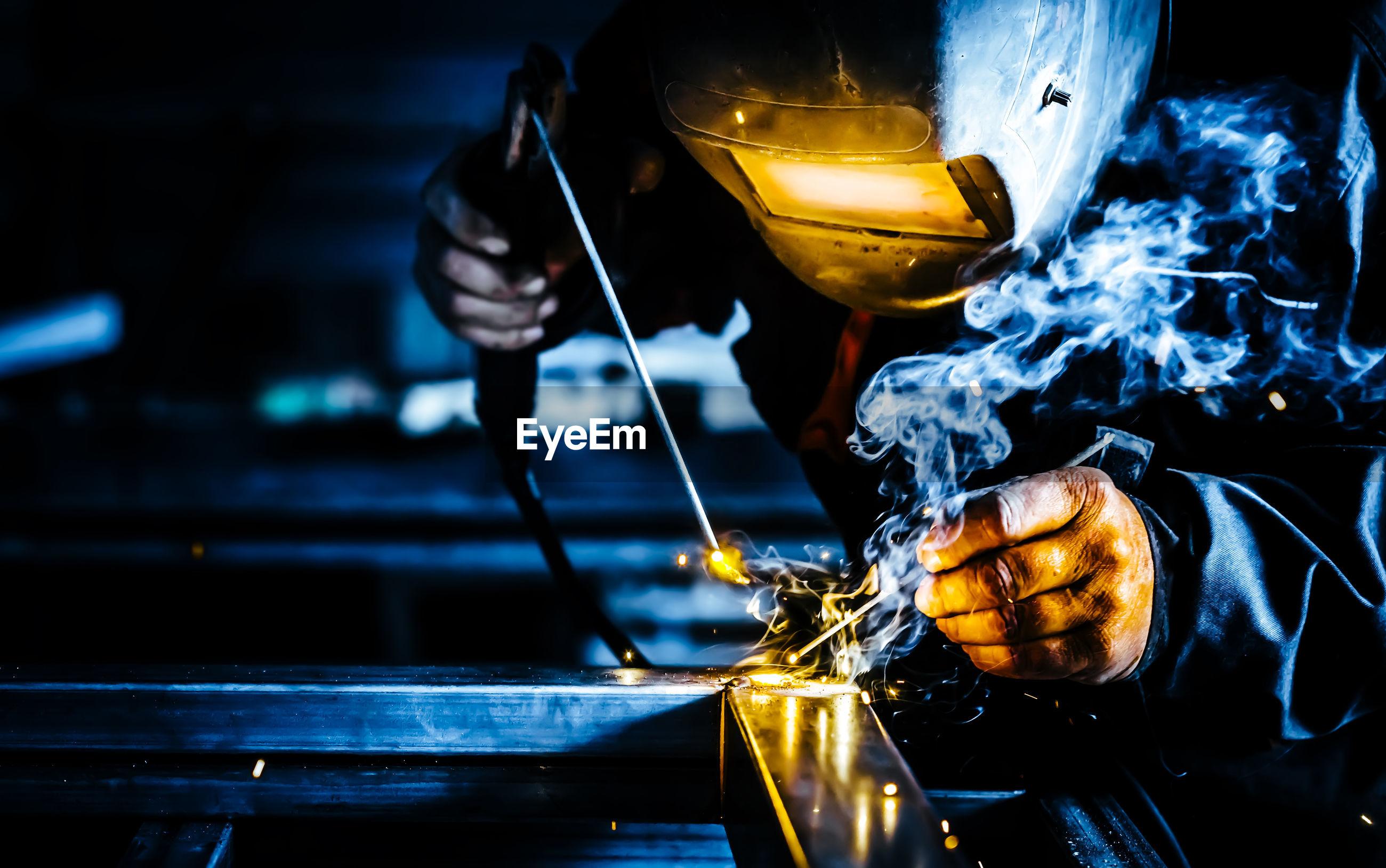 Worker welding metal in factory