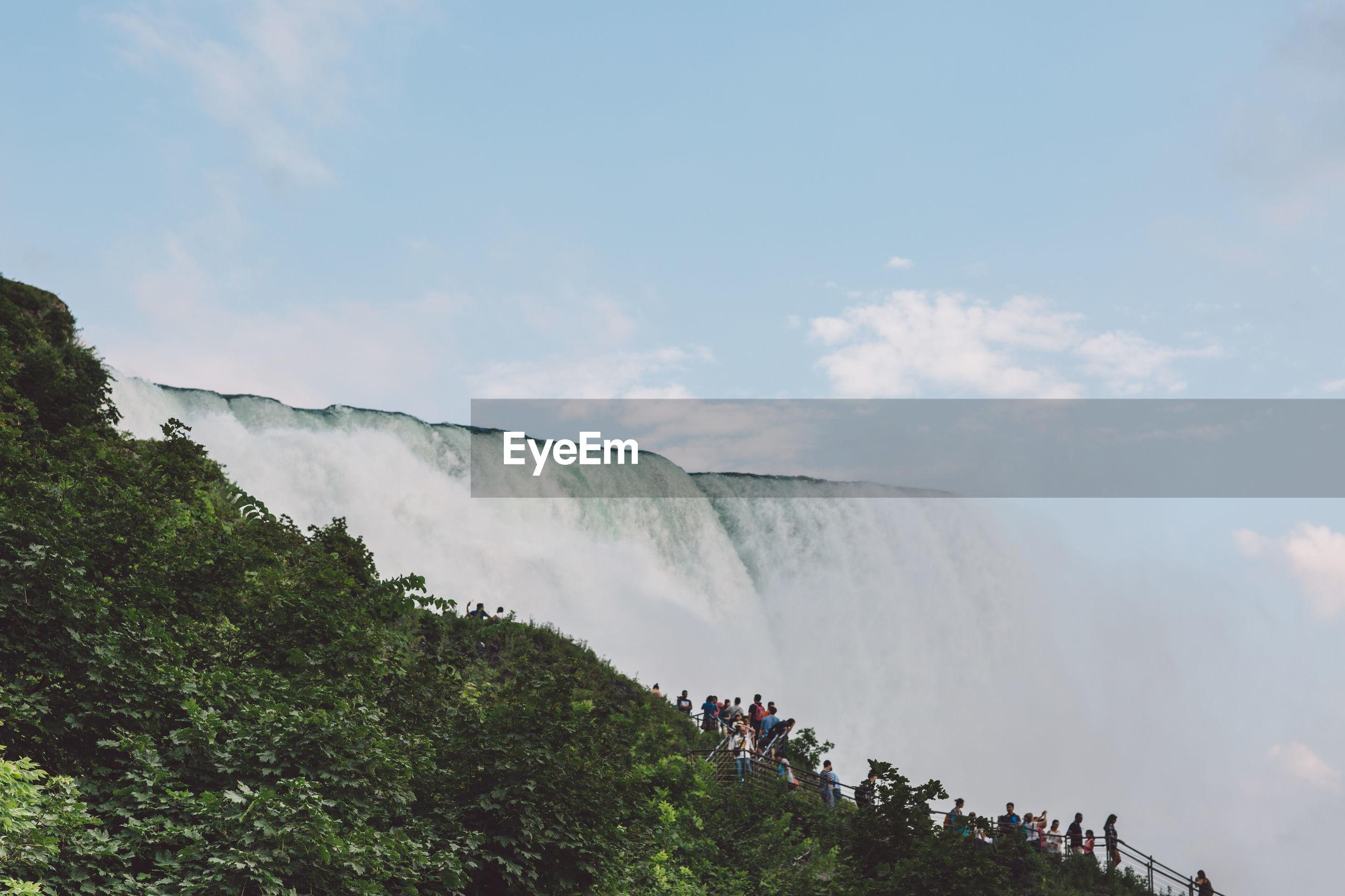 People by waterfall against sky