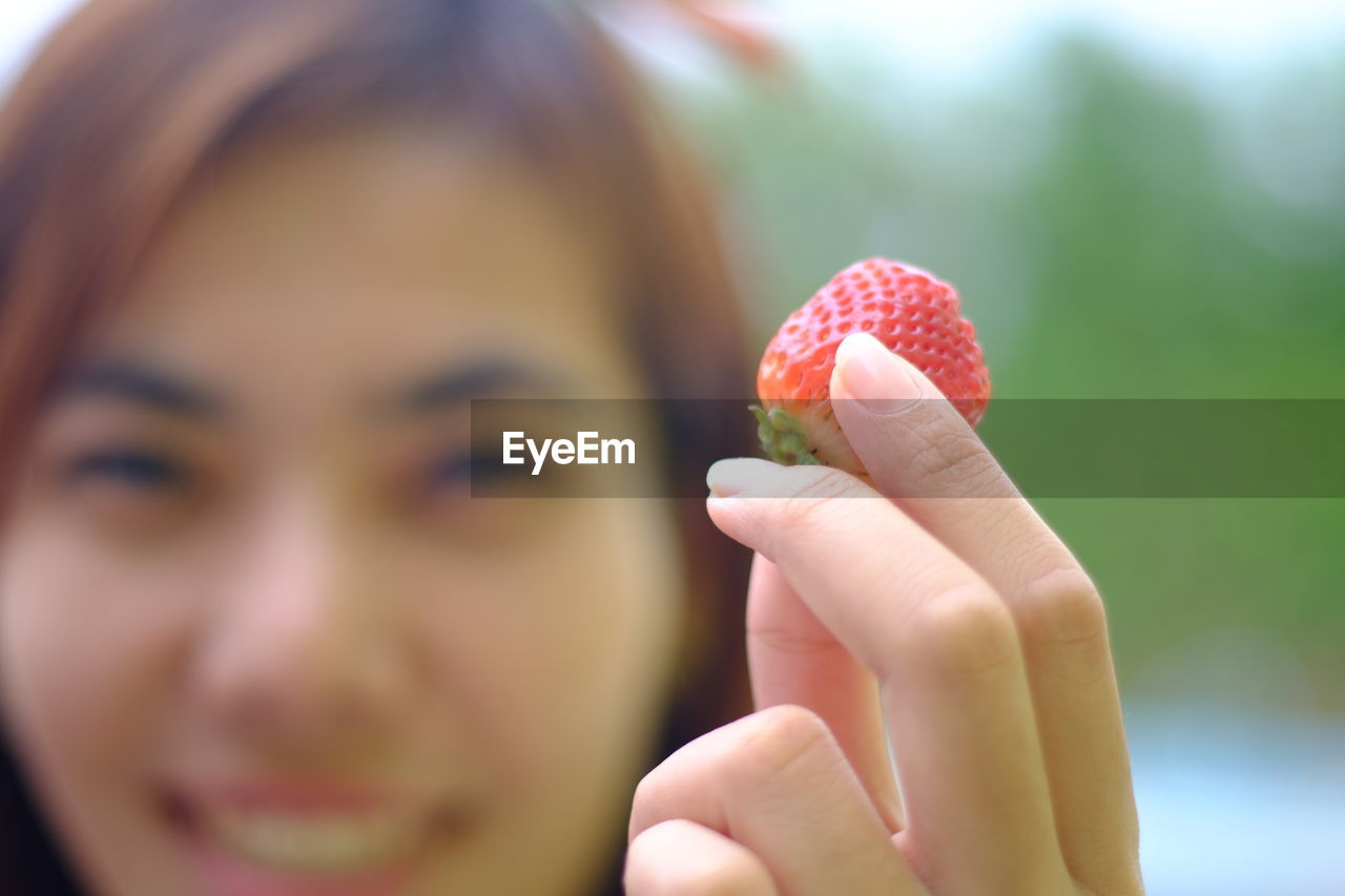 food and drink, fruit, berry fruit, one person, food, real people, healthy eating, human hand, strawberry, holding, human body part, hand, close-up, freshness, focus on foreground, women, leisure activity, wellbeing, lifestyles, finger, body part