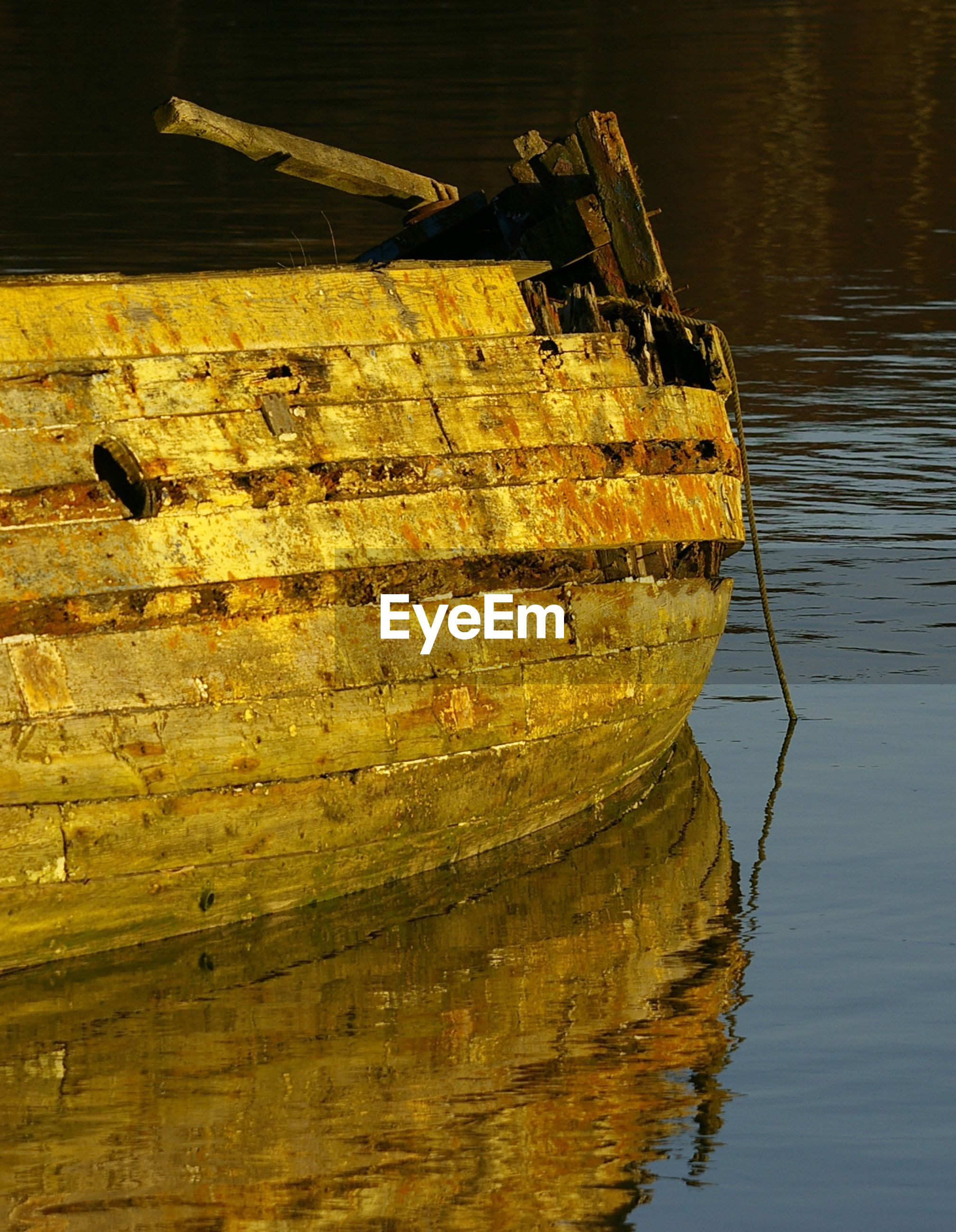 water, yellow, reflection, lake, nautical vessel, calm, cropped, boat, rippled, close-up, plank, in a row, waterfront, ocean, tranquility, no people, stone, weathered, day, sea, surface level, tranquil scene, lakeside