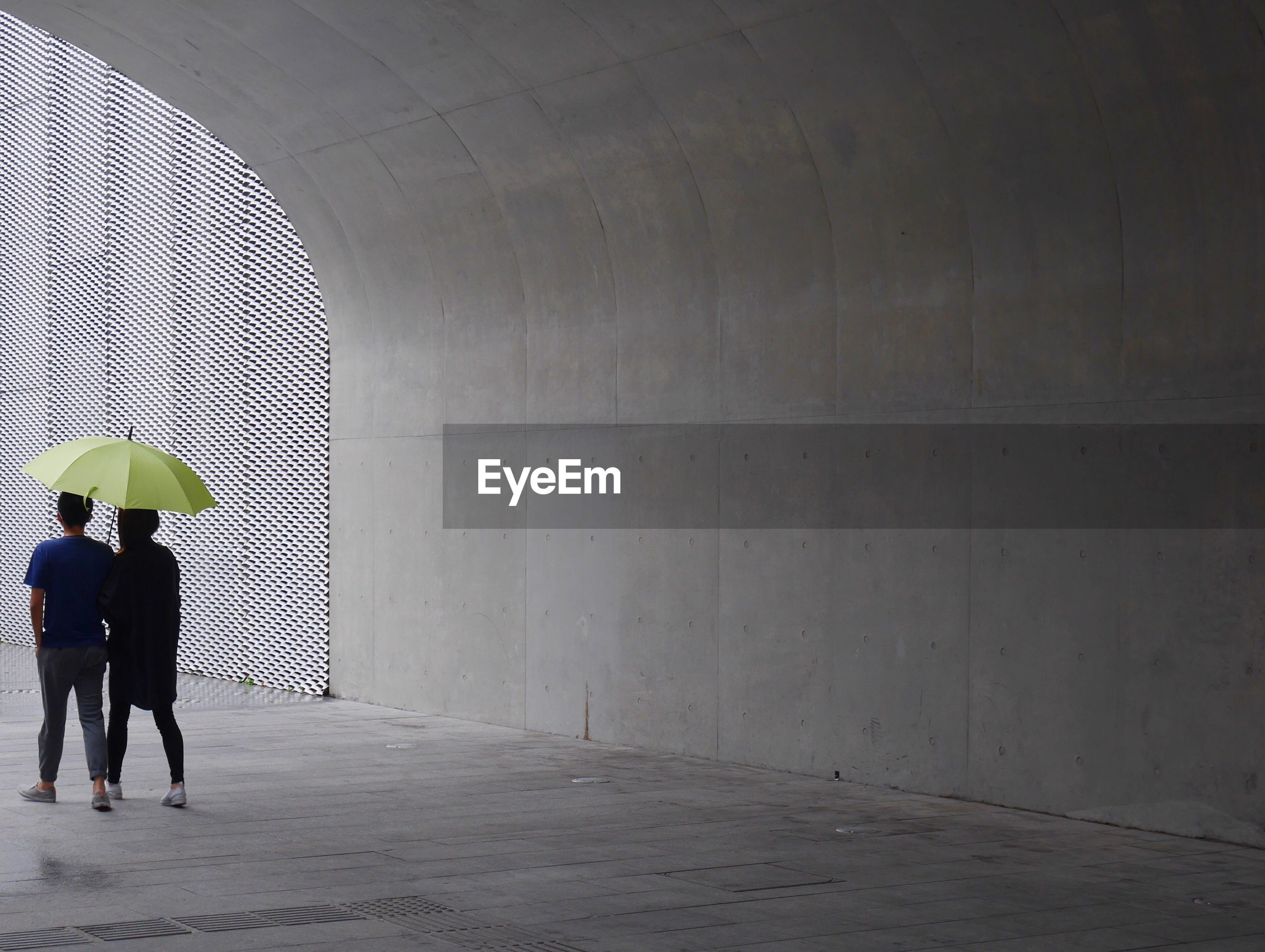 Rear view full length of people with umbrella below bridge during rainy season