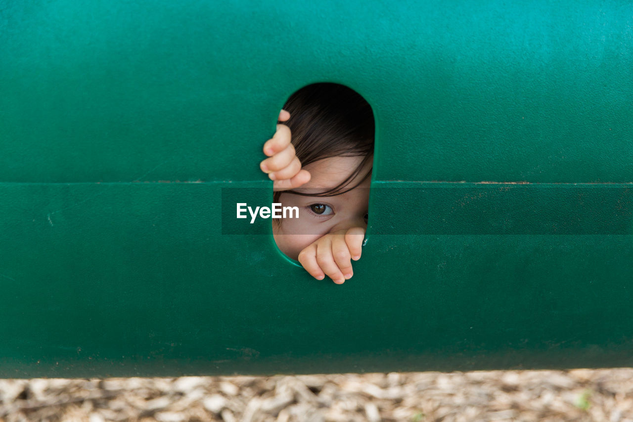 Close-Up Of Portrait Of Child Looking Through Hole