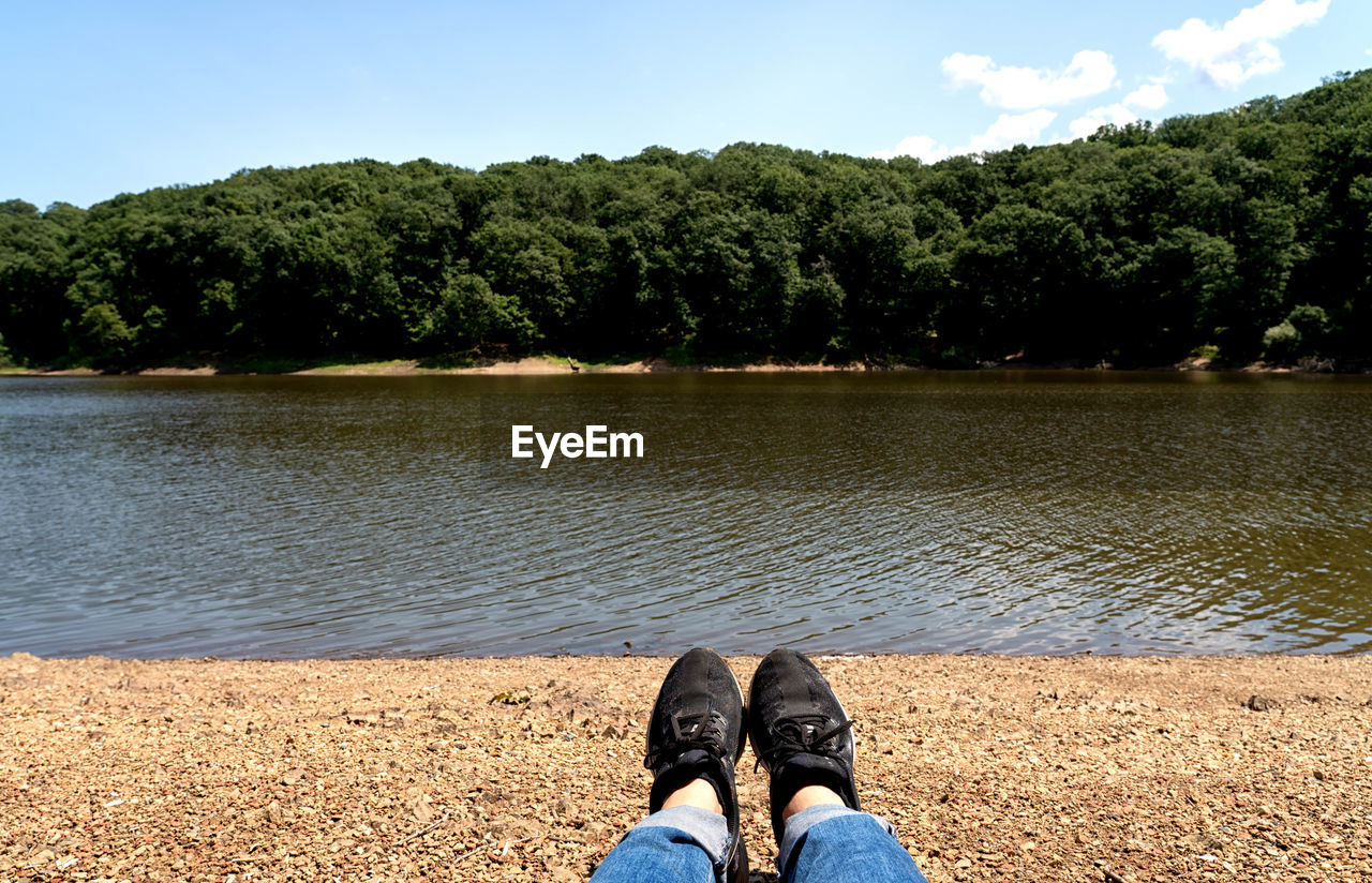 water, low section, tree, human leg, plant, body part, real people, human body part, personal perspective, shoe, nature, lake, one person, lifestyles, day, beauty in nature, sky, leisure activity, unrecognizable person, outdoors, human foot