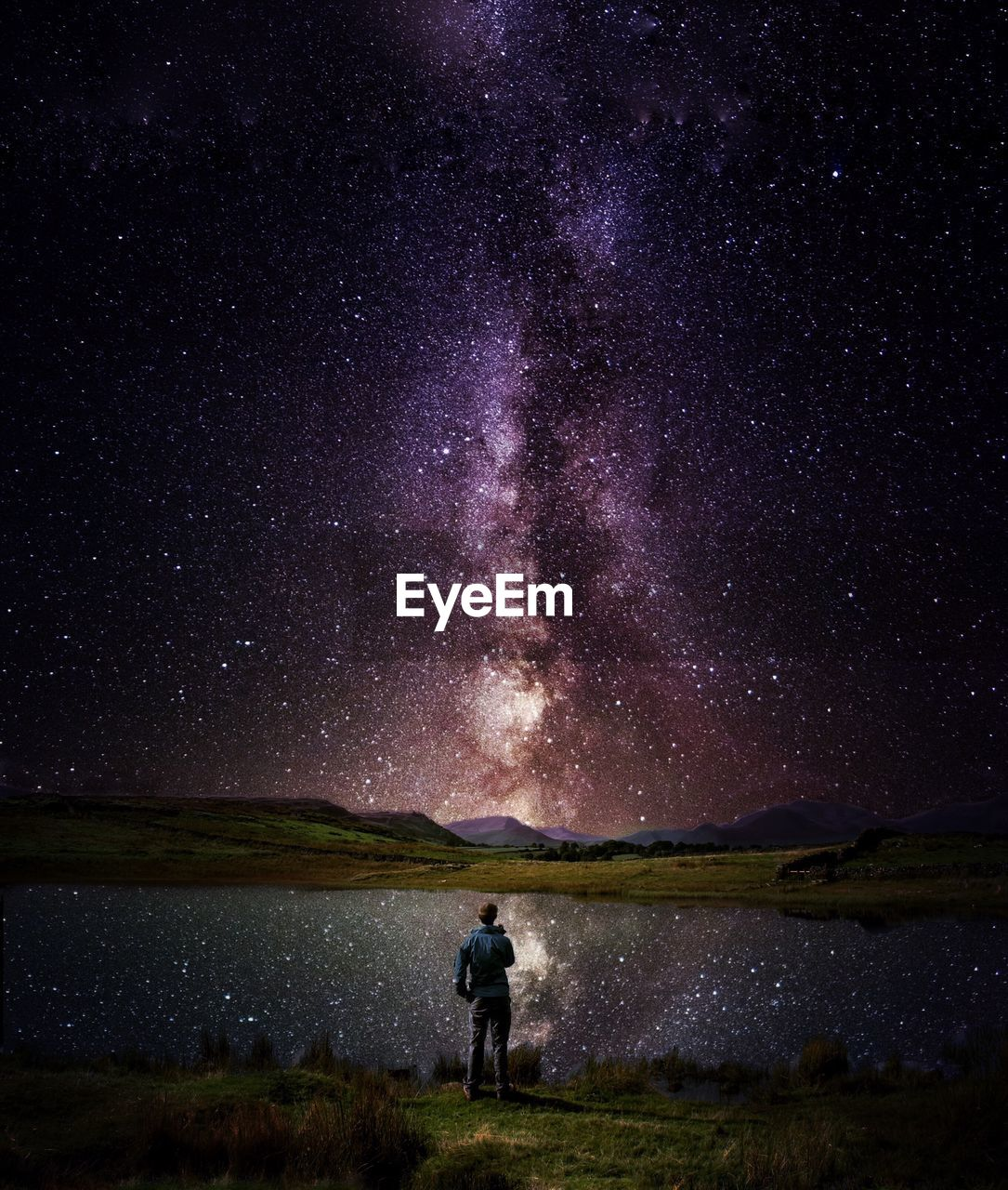 Rear View Of Man Standing By Lake Against Star Field