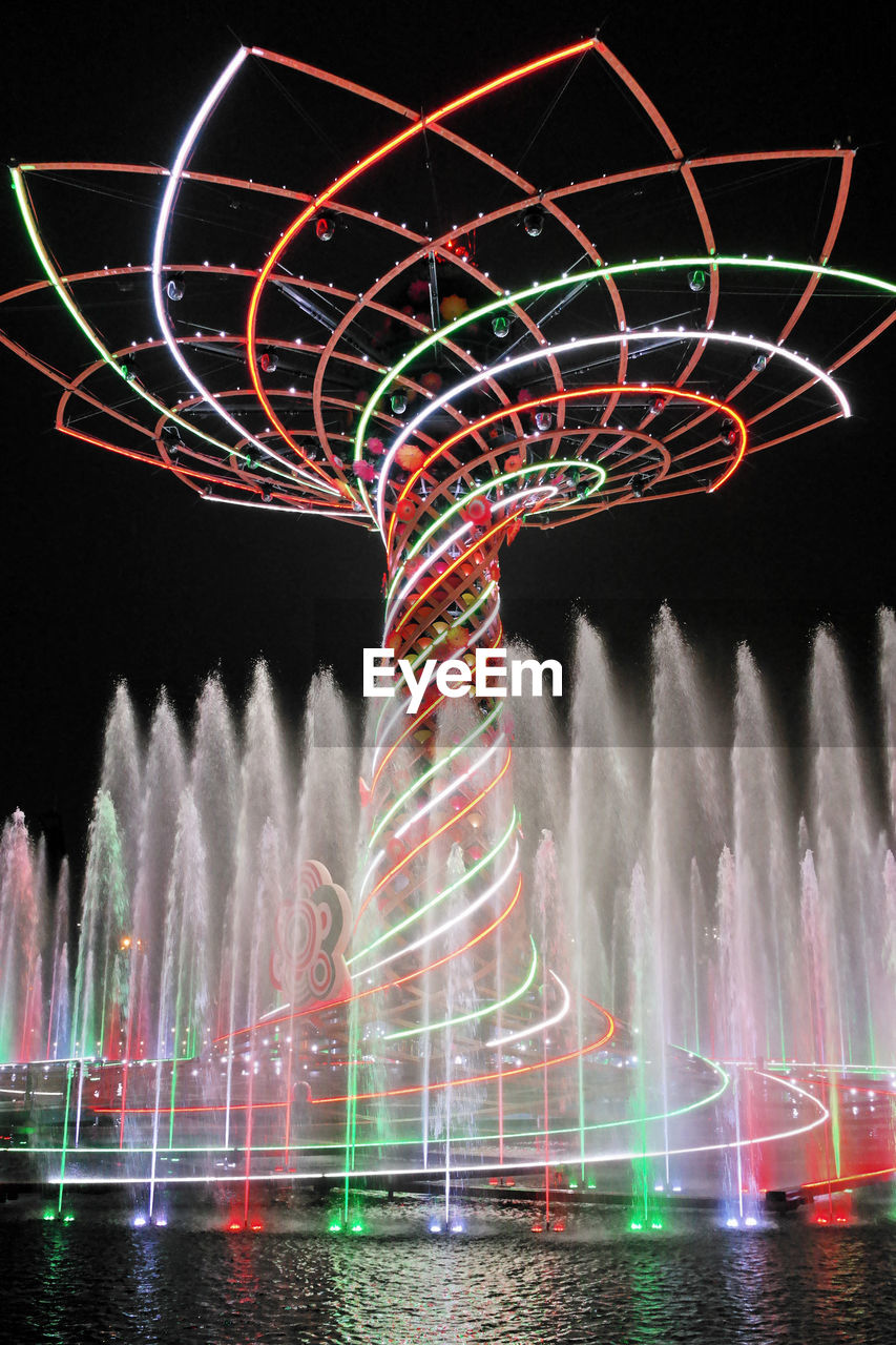 LOW ANGLE VIEW OF ILLUMINATED FOUNTAIN AGAINST SKY