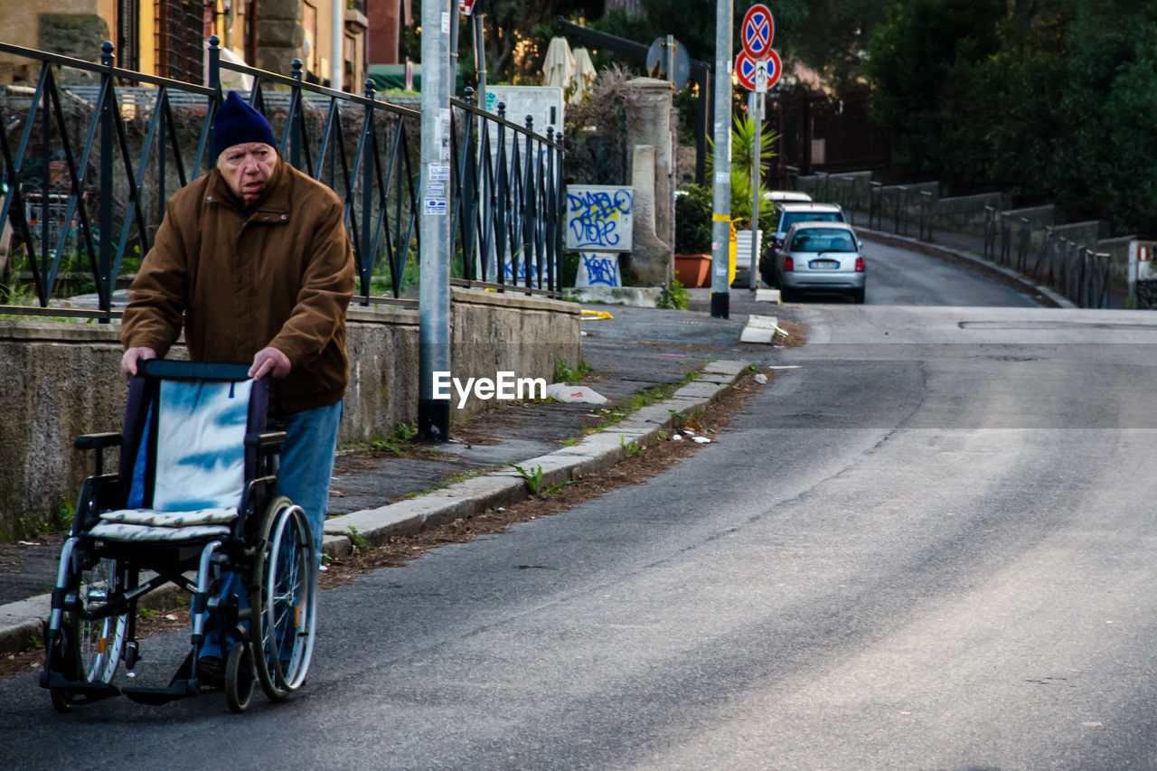 street, road, transportation, one person, real people, mode of transport, outdoors, land vehicle, car, full length, day, city, sitting, men, physical impairment, wheelchair, one man only, adult, adults only, people