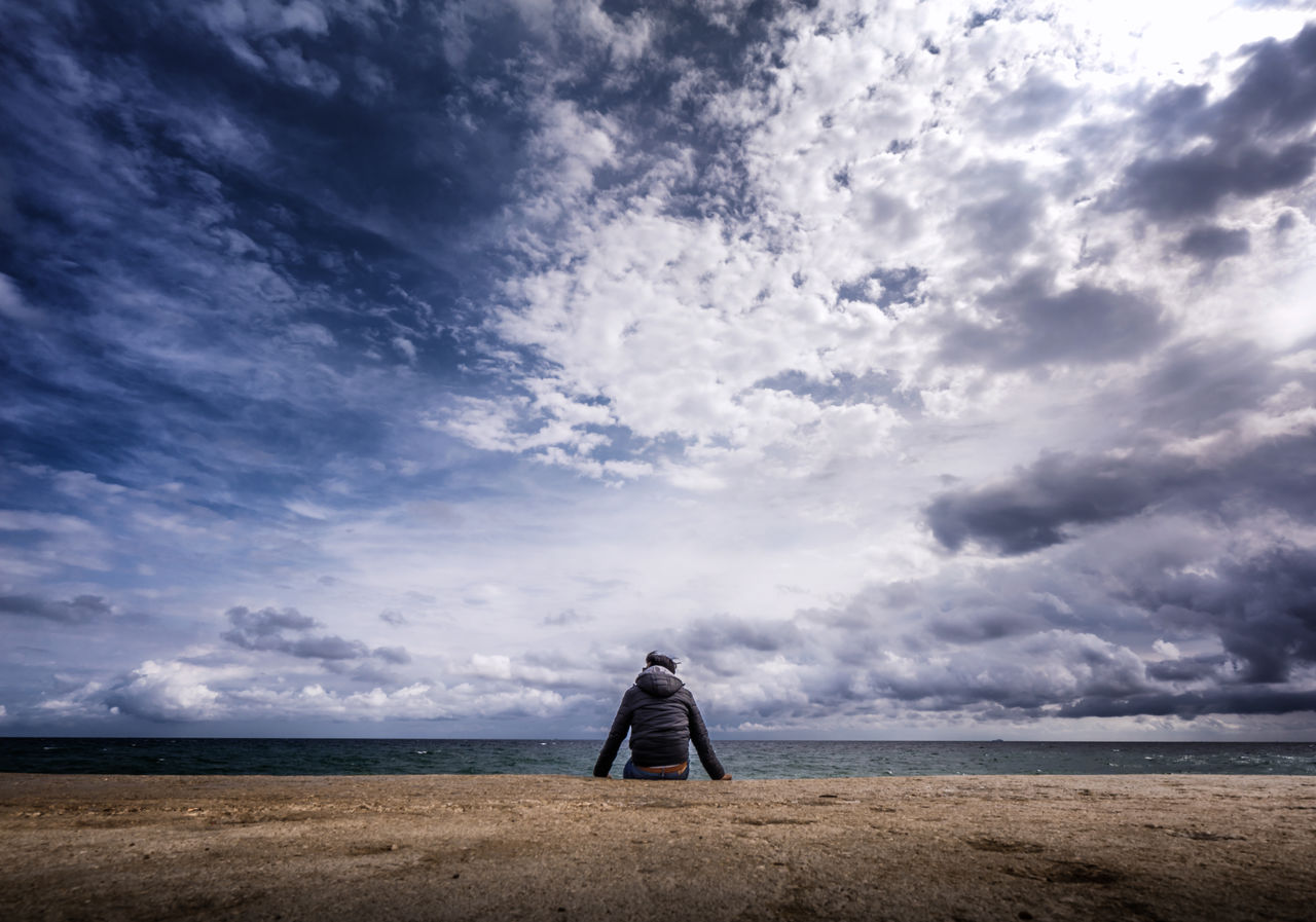 Rear View Of Man Sitting At Seaside Against Cloudy Sky