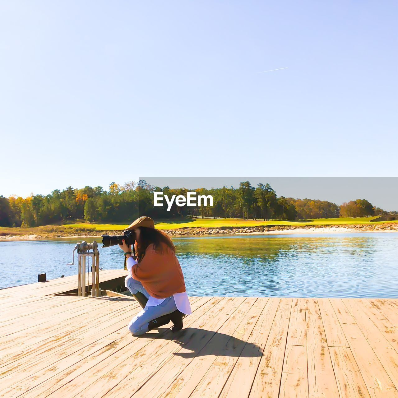 Woman photographing while kneeling on pier at lake against sky