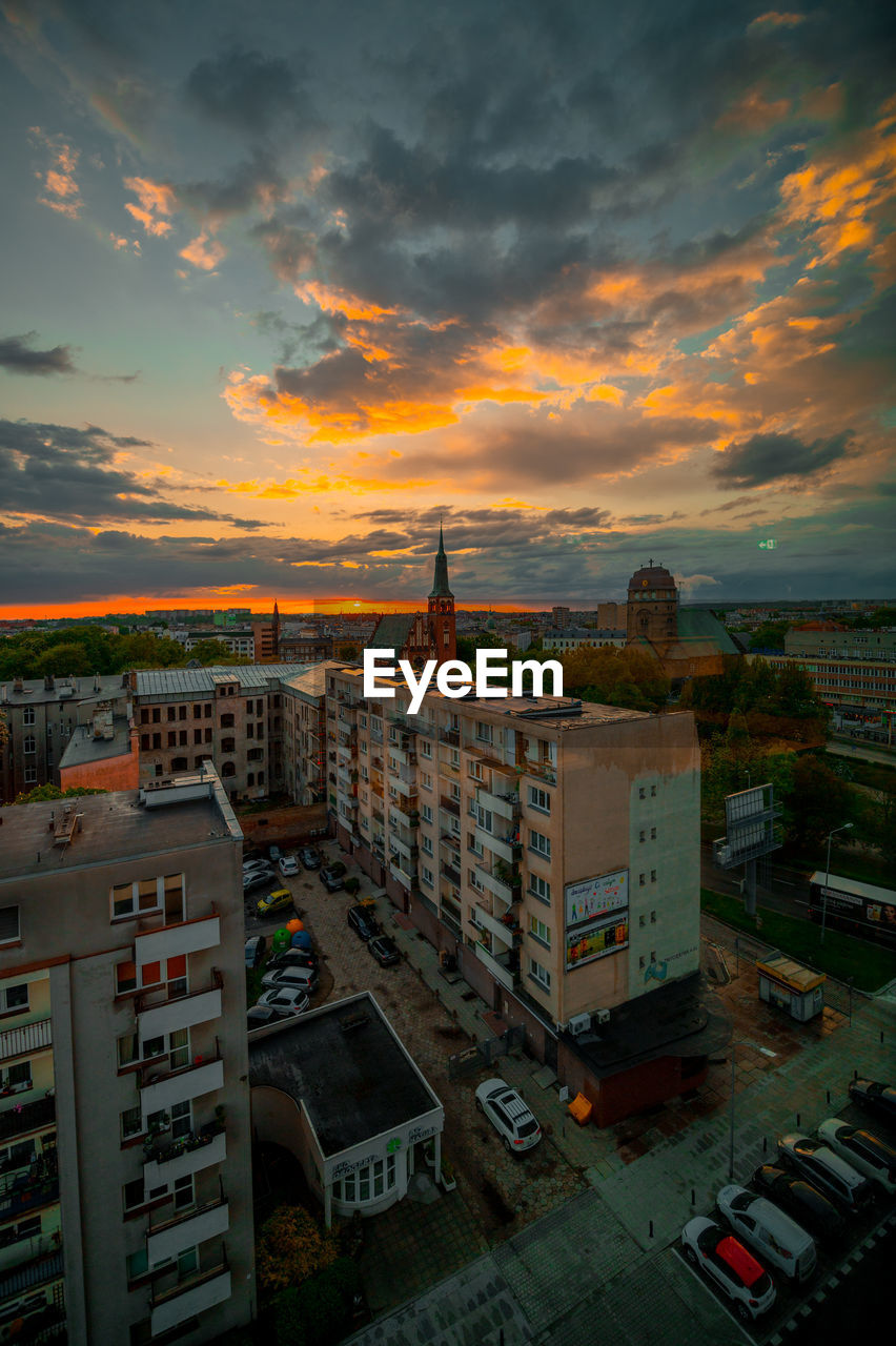 HIGH ANGLE VIEW OF BUILDINGS AGAINST CLOUDY SKY DURING SUNSET