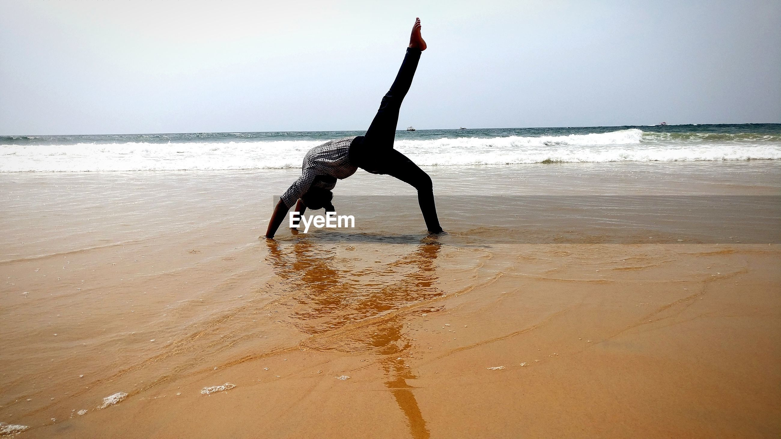 Woman doing stunt in sea against clear sky