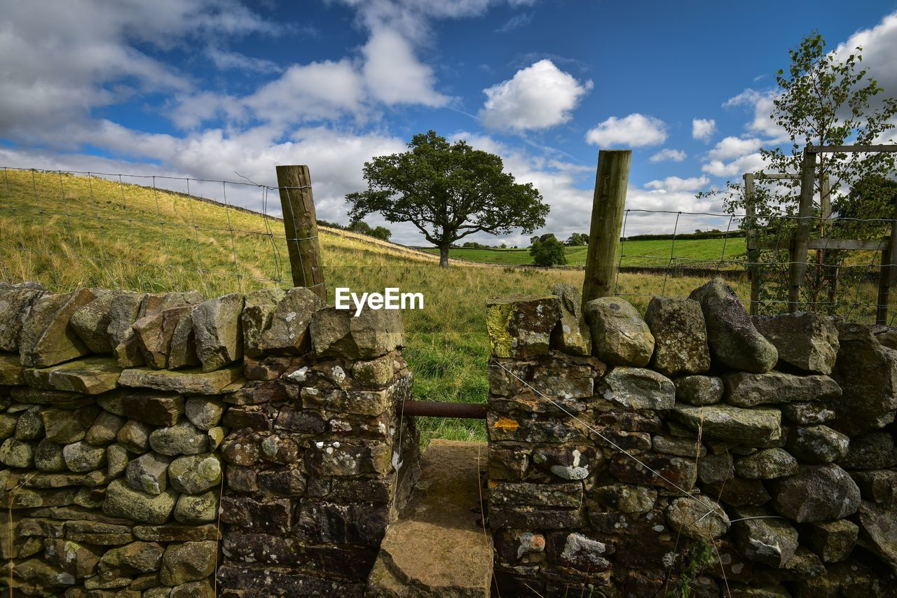 sky, cloud - sky, stone wall, plant, nature, solid, wall, tree, no people, grass, day, architecture, history, fence, land, barrier, boundary, ancient, the past, tranquil scene, stone material, outdoors, ancient civilization
