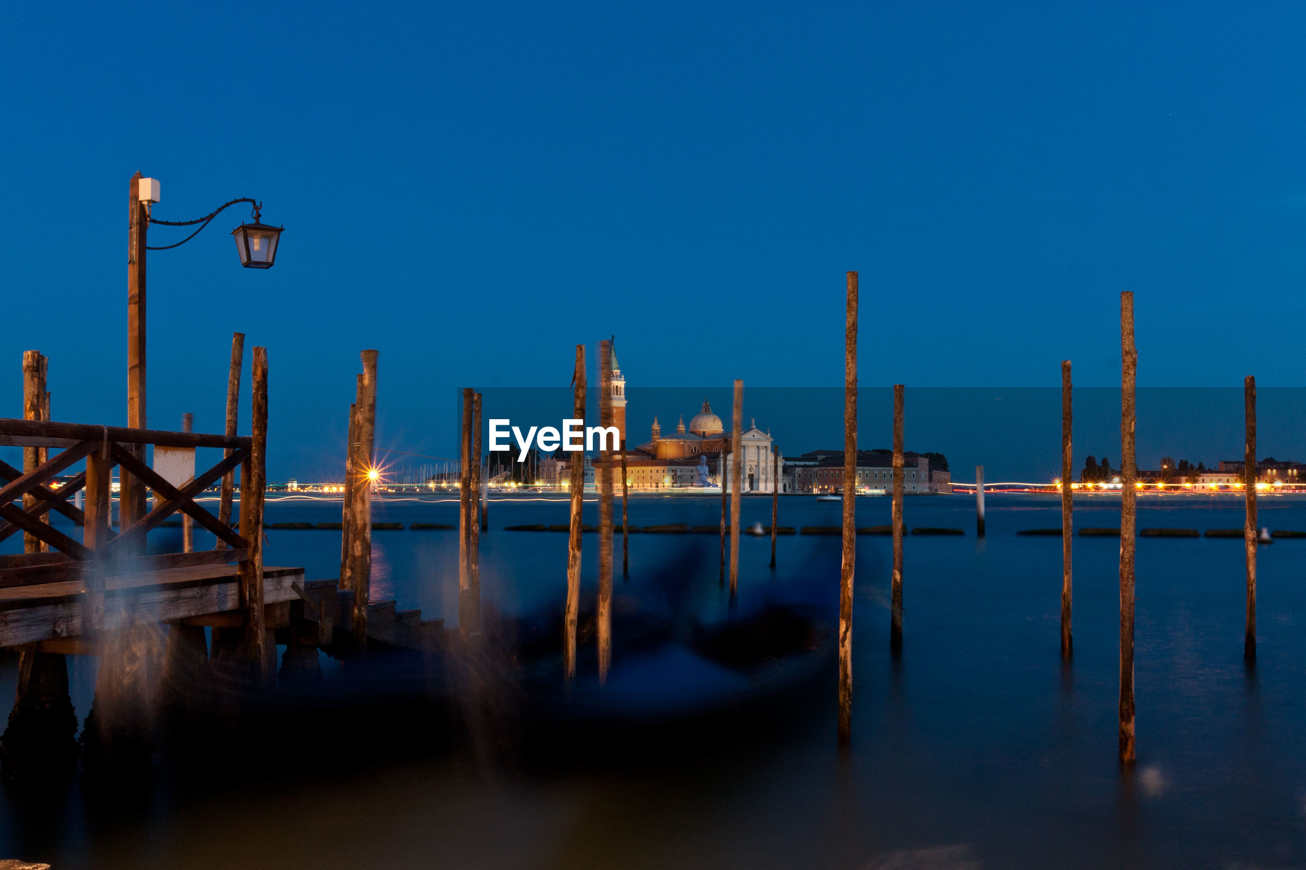Wooden posts in grand canal at night