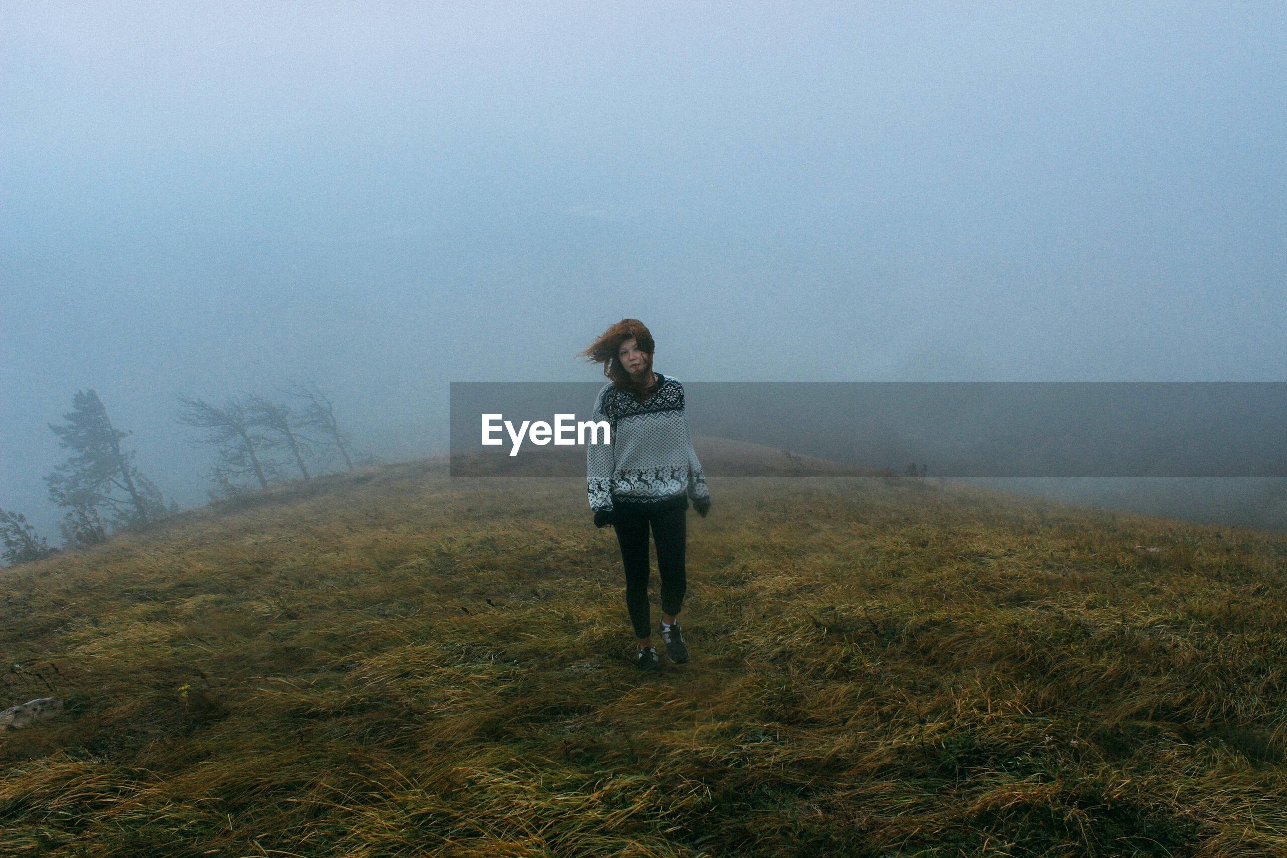 Full length of woman walking on field during foggy weather