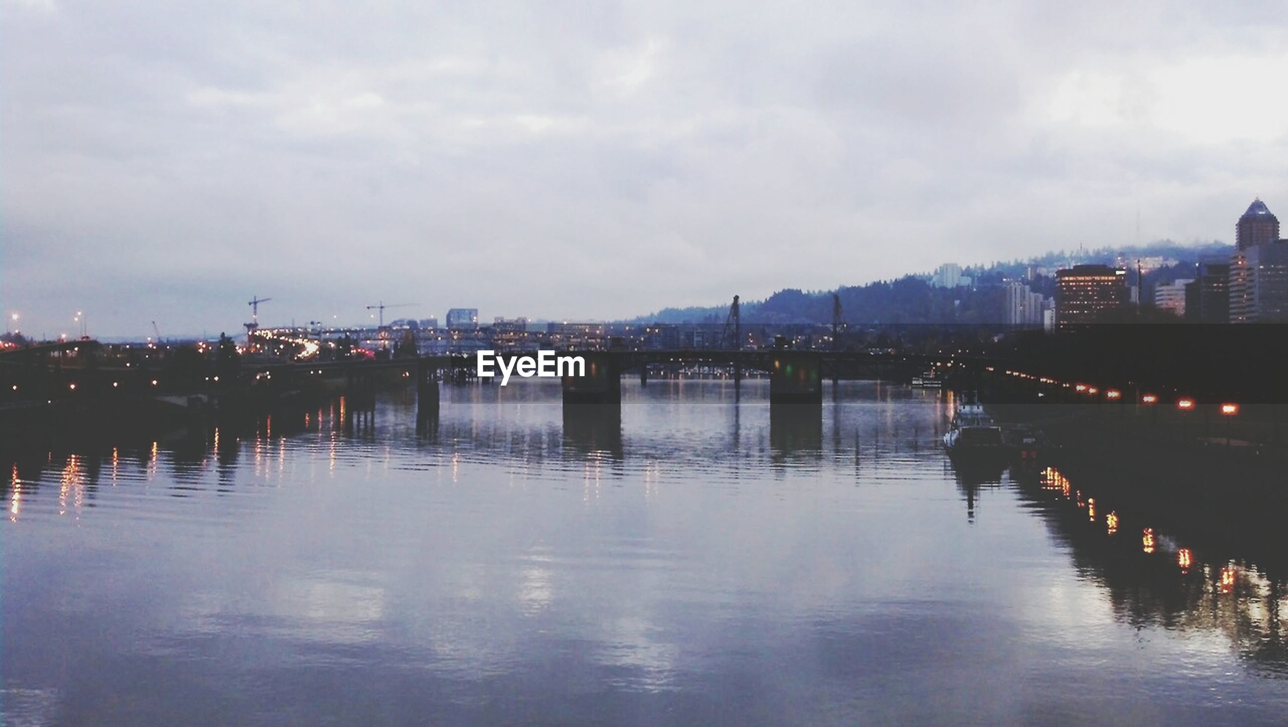water, architecture, built structure, building exterior, sky, waterfront, reflection, river, cloud - sky, illuminated, city, cloudy, dusk, cloud, outdoors, bridge - man made structure, lake, connection, residential building, transportation
