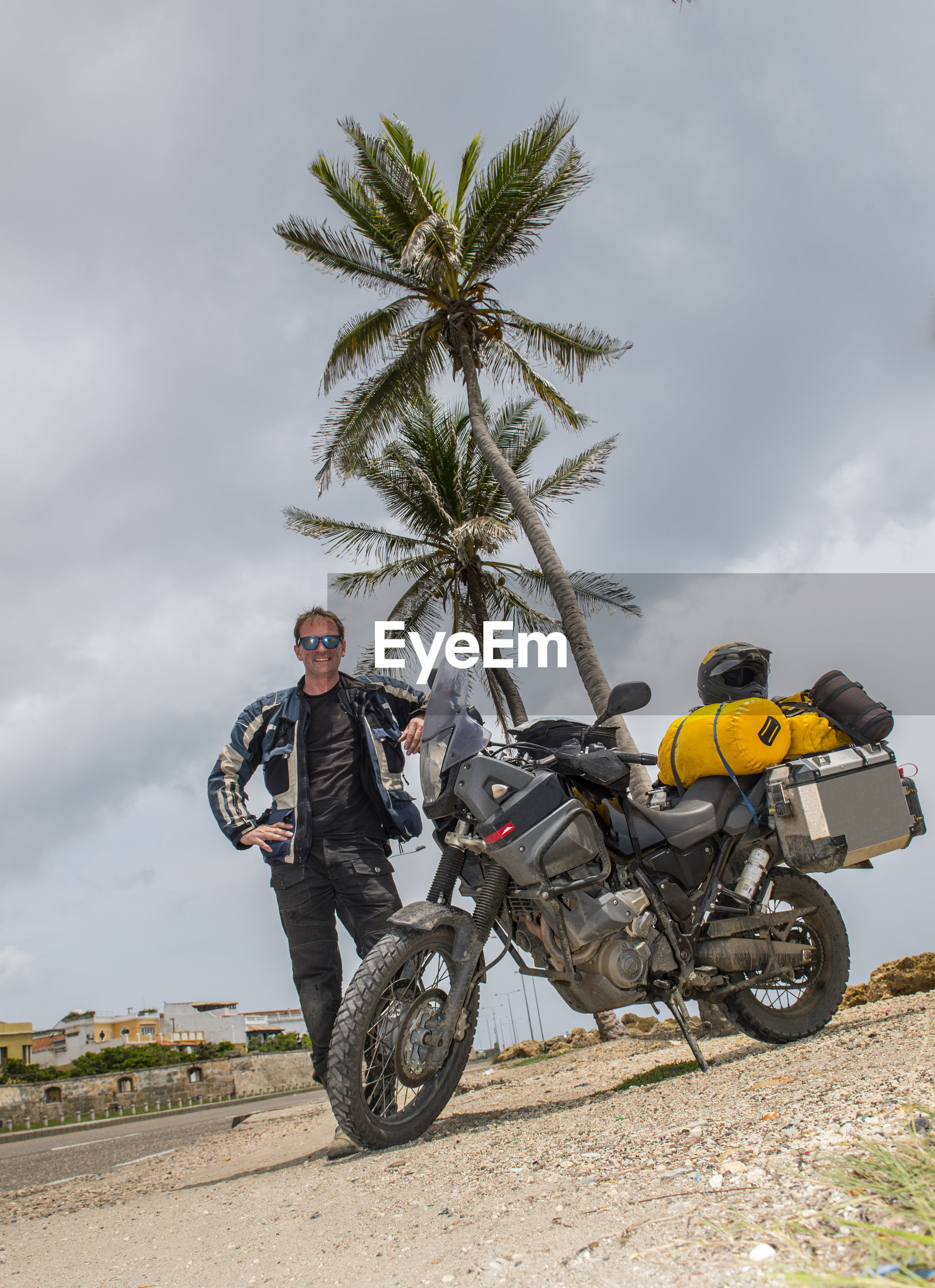 MAN RIDING MOTORCYCLE AGAINST SKY